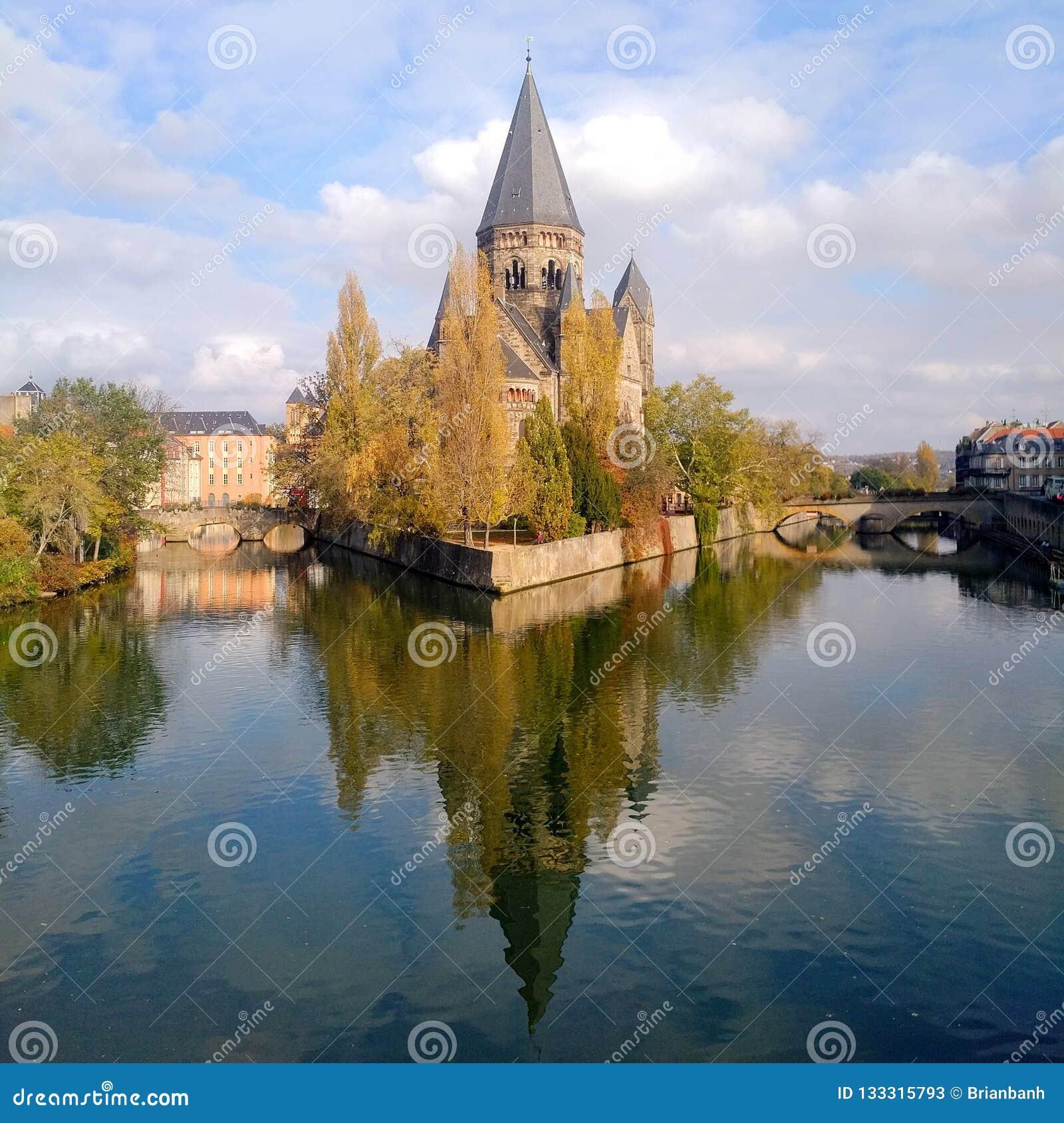 Spokojny dzień z Świątynnym Neuf odbija nad wodą w Metz, Francja