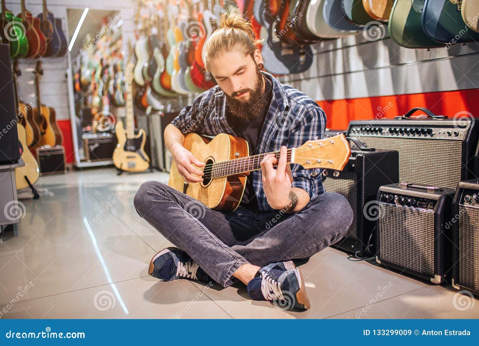Spokojny i skoncentrowany młody człowiek siedzi na podłodze z nogami krzyżować On playes na gitarze akustycznej Wiele gitary elek
