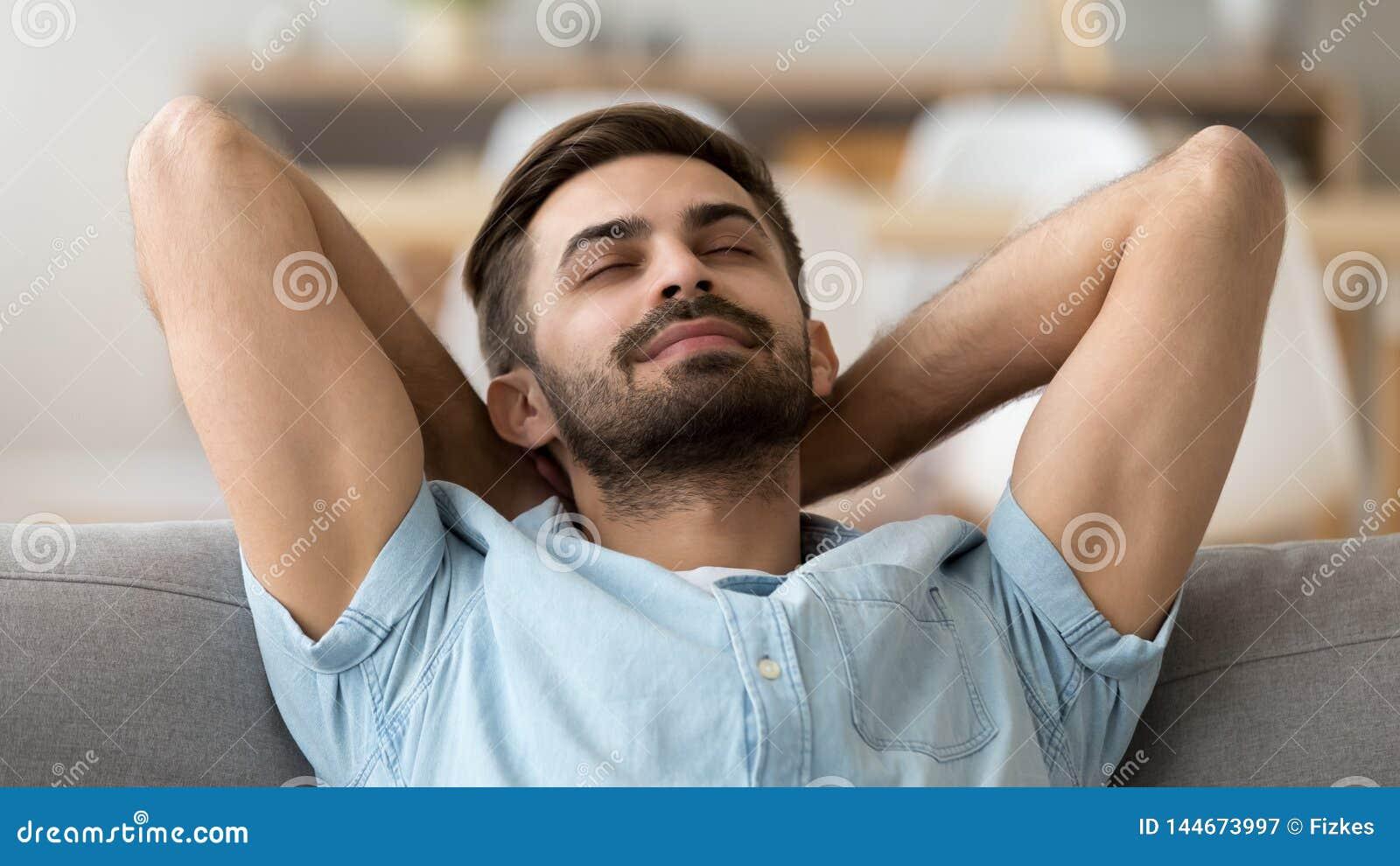 Spokojny pokojowy mężczyzna relaksuje z zamkniętymi oczami opartymi na kanapie z powrotem