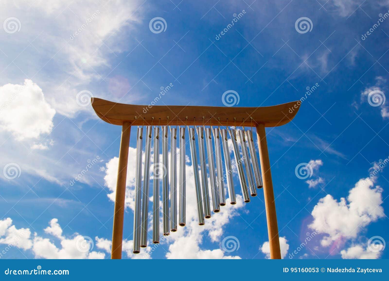 Spola musikaliska chimes på bakgrunden av blå himmel