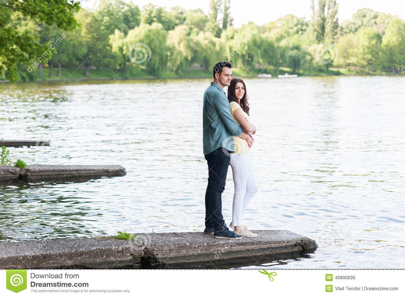 Spontaneous couple in love embraced on a stone pier