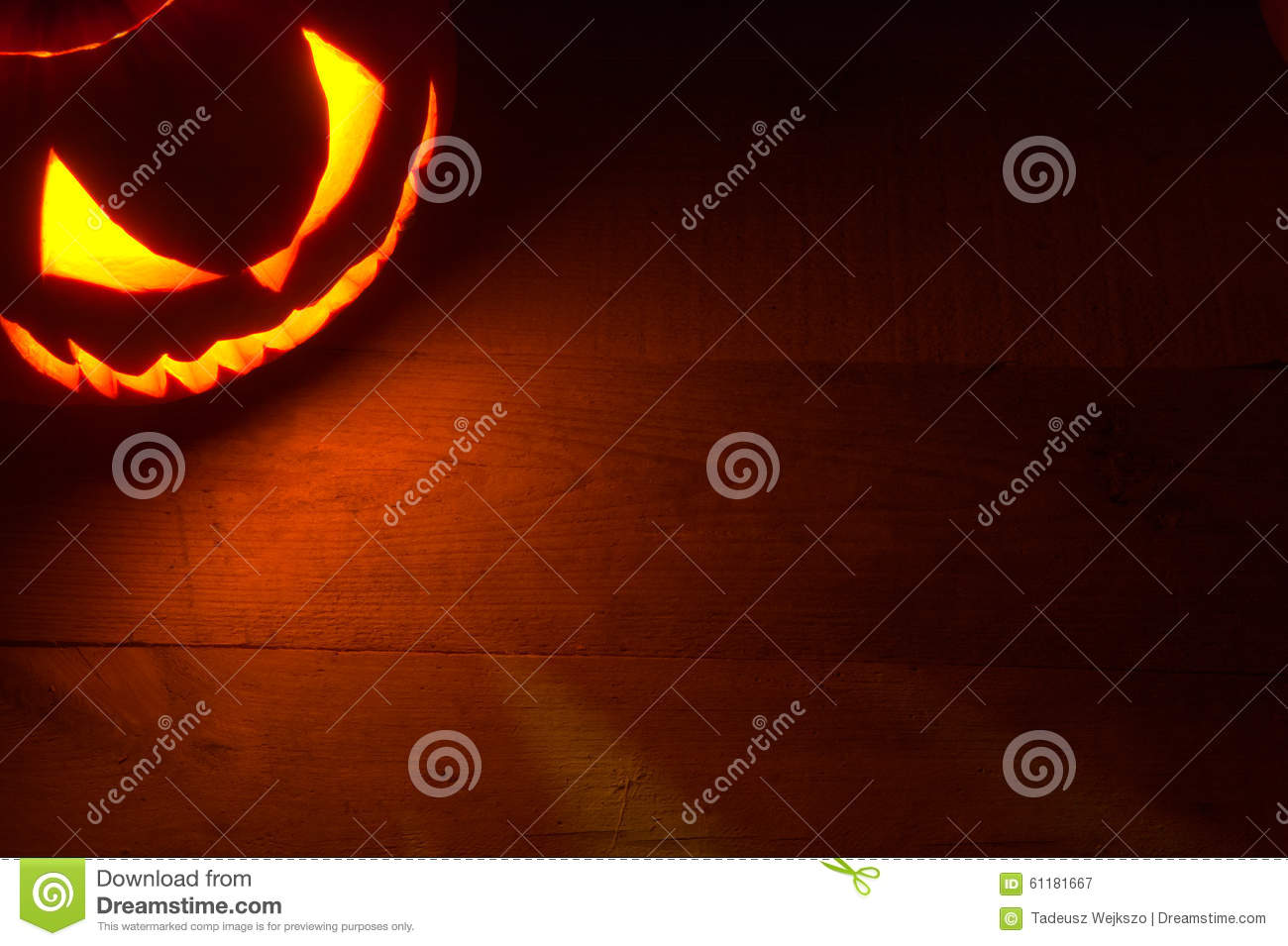 Spooky halloween background with evil face of jack o lantern in the corner