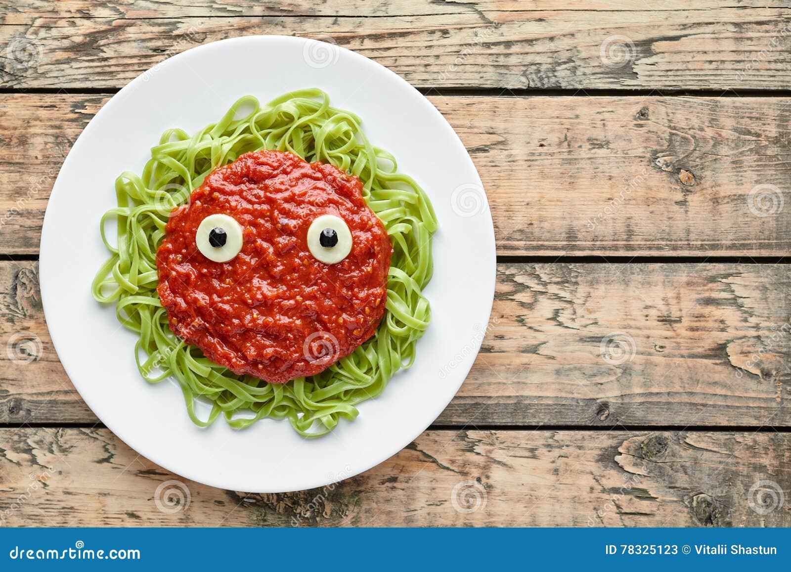 Spooky halloween monster green pasta with fake blood tomato sauce and mozzarella eyeballs