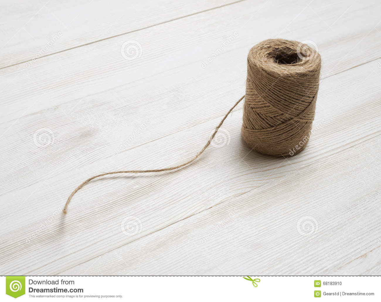 spool of wool thread on a white wooden background top view desktop