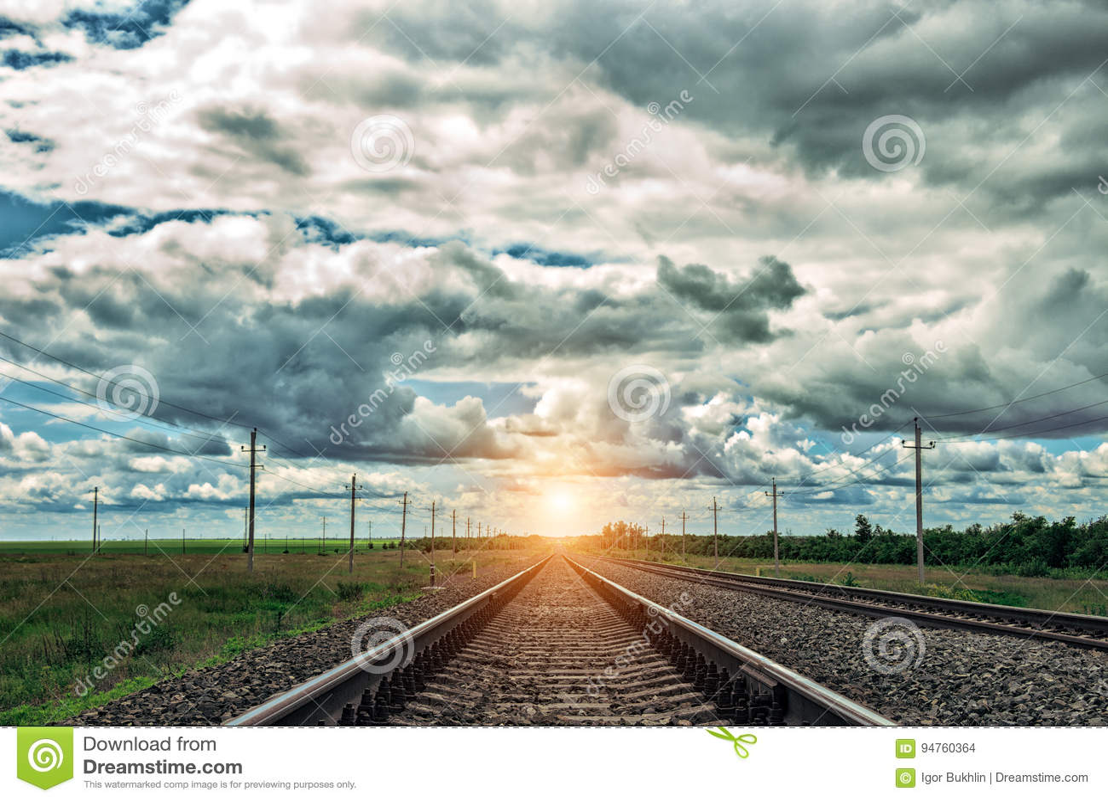 Spoorweg bij zonsondergang met dramatische hemel Het spoor van de spoorweg