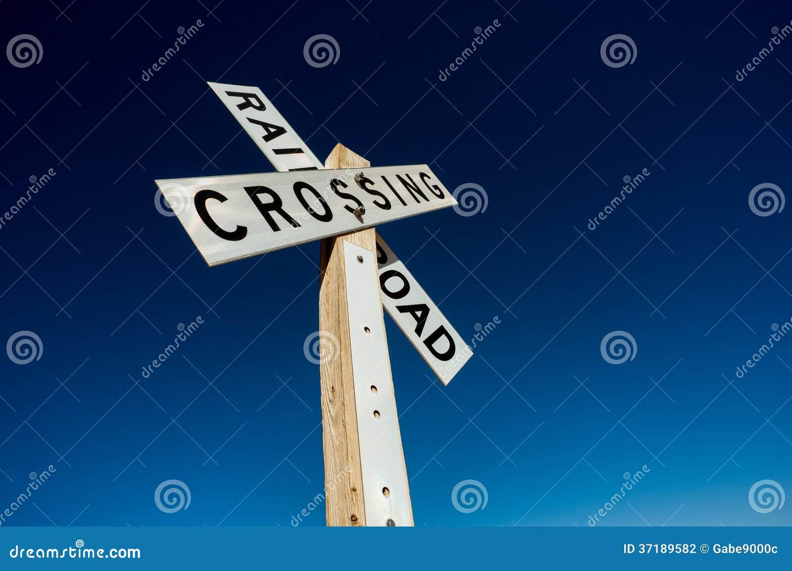 Spoorweg die teken op blauwe hemel kruisen