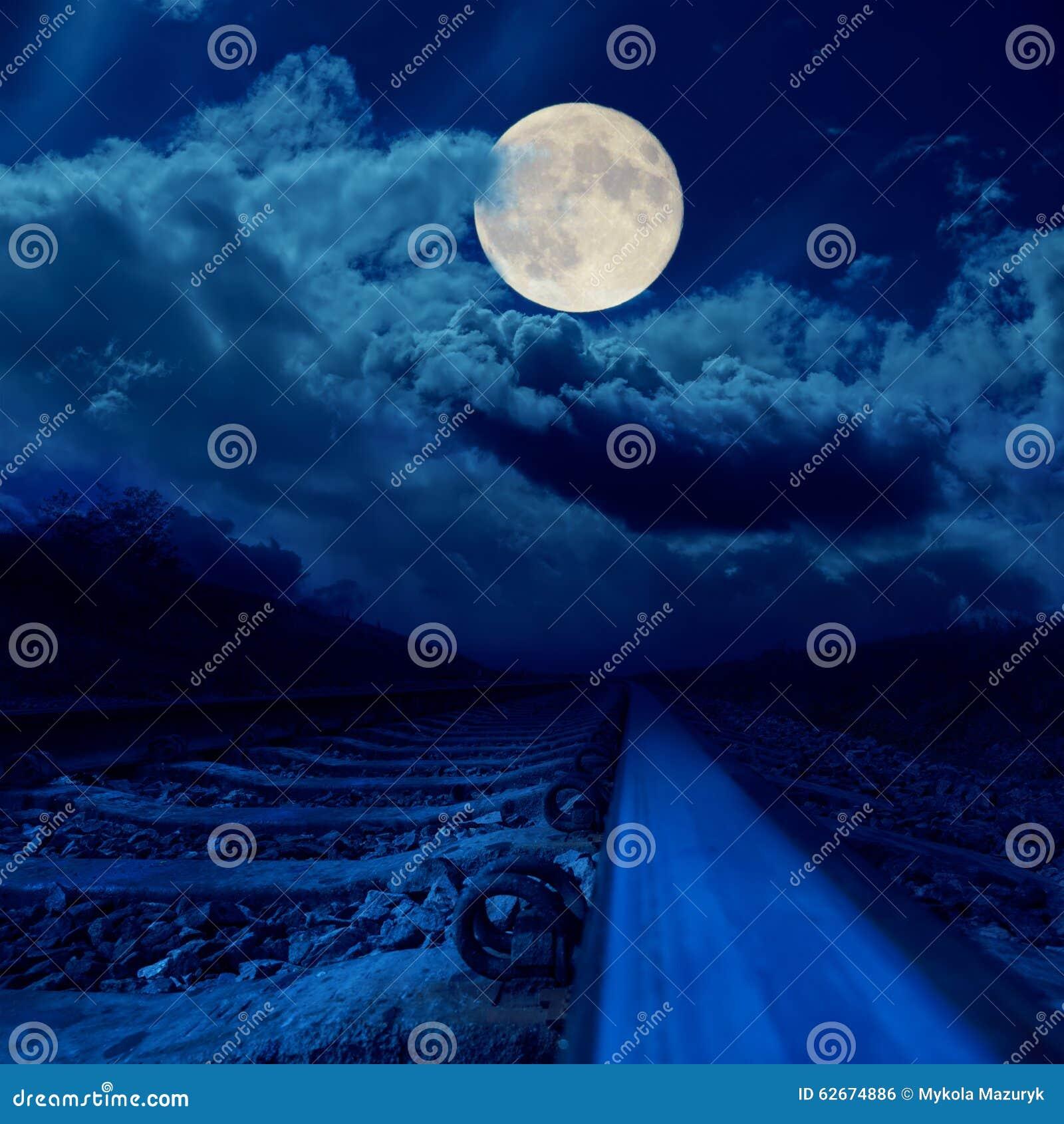 Spoorweg in nacht onder volle maan in wolken