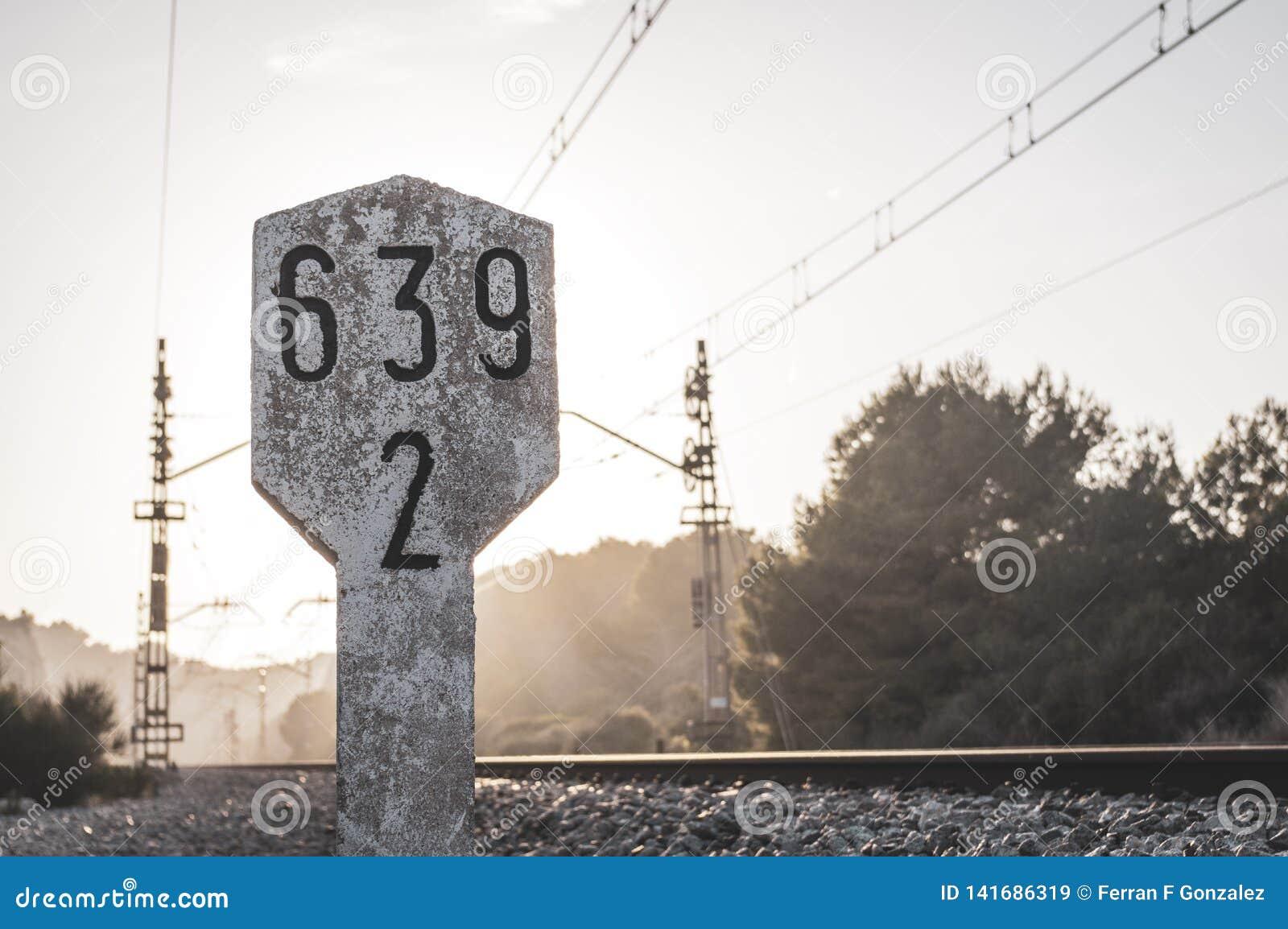 Spoorwegverkeersteken naast treinsporen met kilometric nummering in concrete teller met zonsondergang raylights