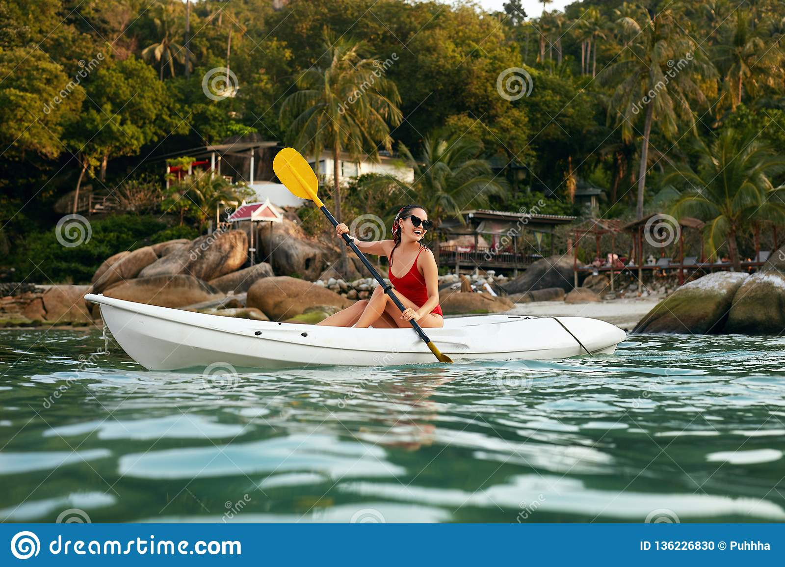 Sport acquatico di estate Donna che viaggia in kajak vicino all isola verde