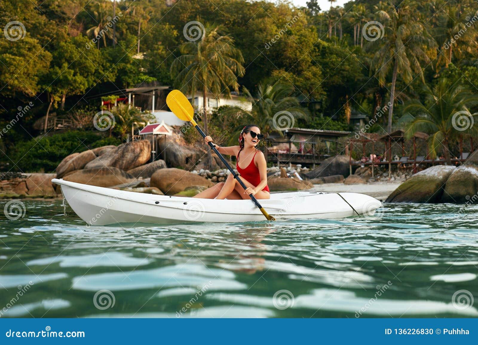 Sport aquatique d été Femme voyageant dans le kayak près de l île verte
