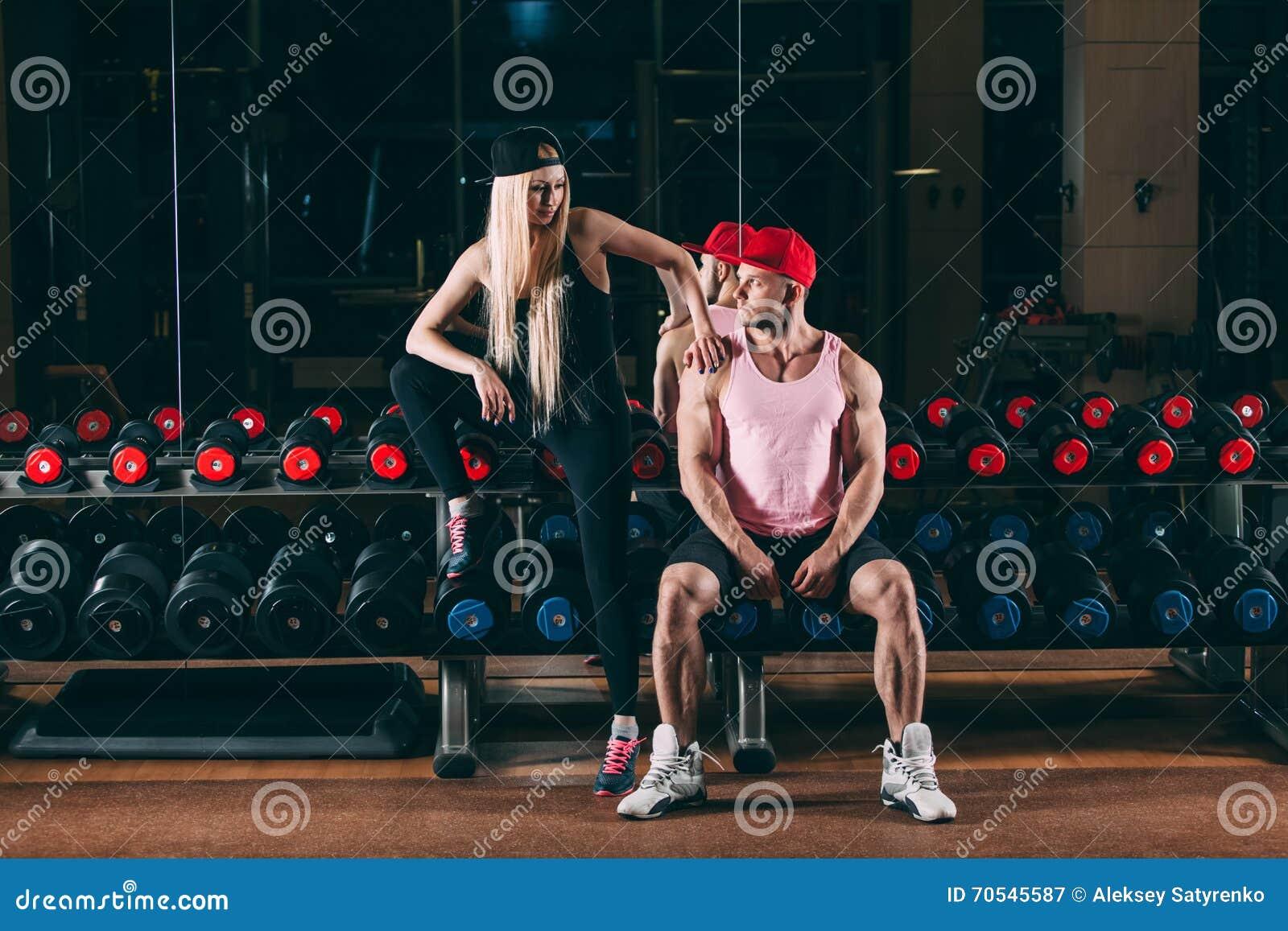 Sport, bodybuilding, tyngdlyftning, livsstil och folkbegrepp - ungt härligt par i stilfull kläder som sitter a
