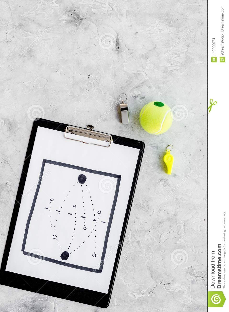 Sport coach concept. Pad with tactic plan of the match near whistle and tennis ball on stone background top view copy