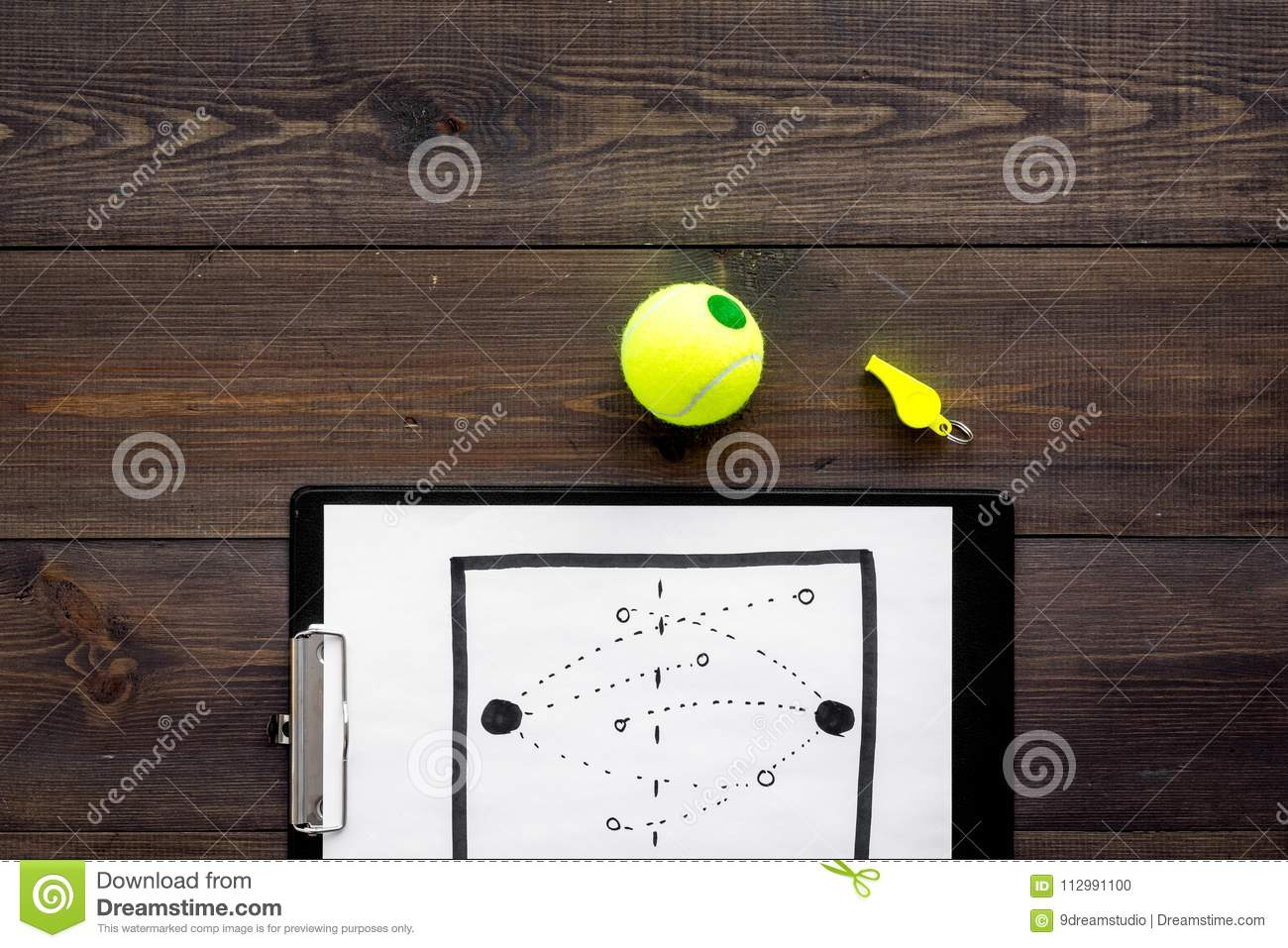 Sport coach concept. Pad with tactic plan of the match near whistle and tennis ball on wooden background top view copy