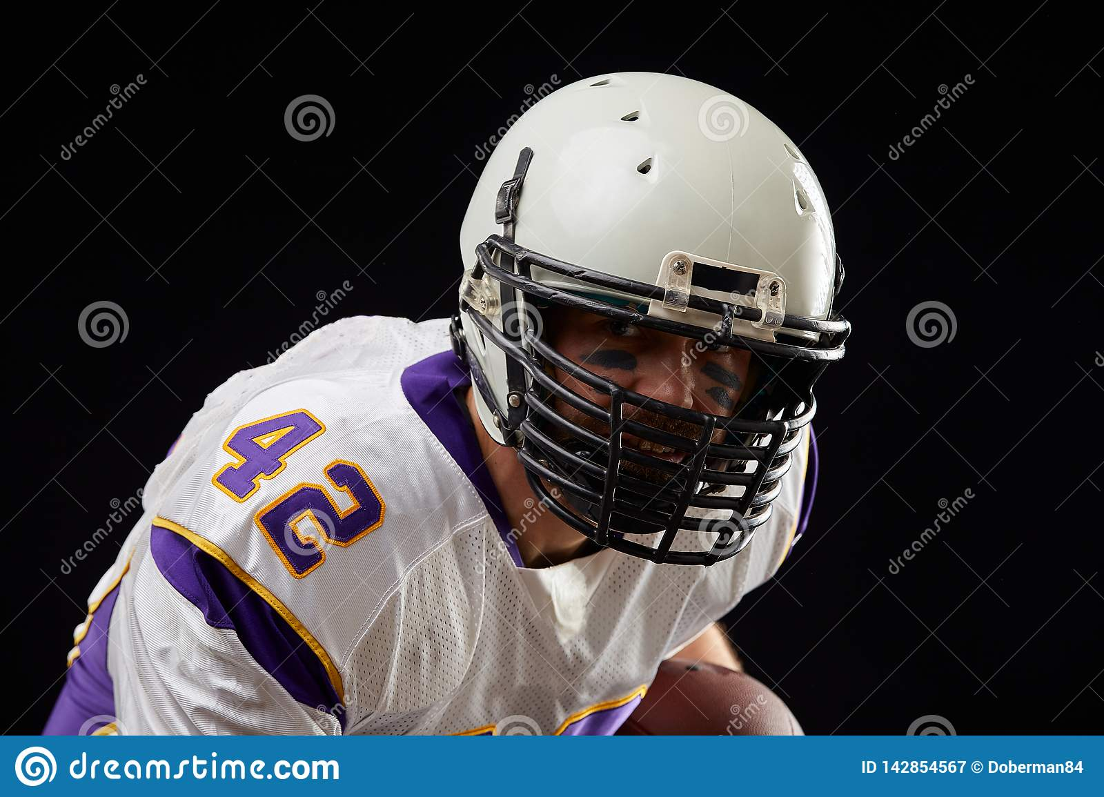 Close up portrait of American football sportsman player in action on black background. Sport concept.