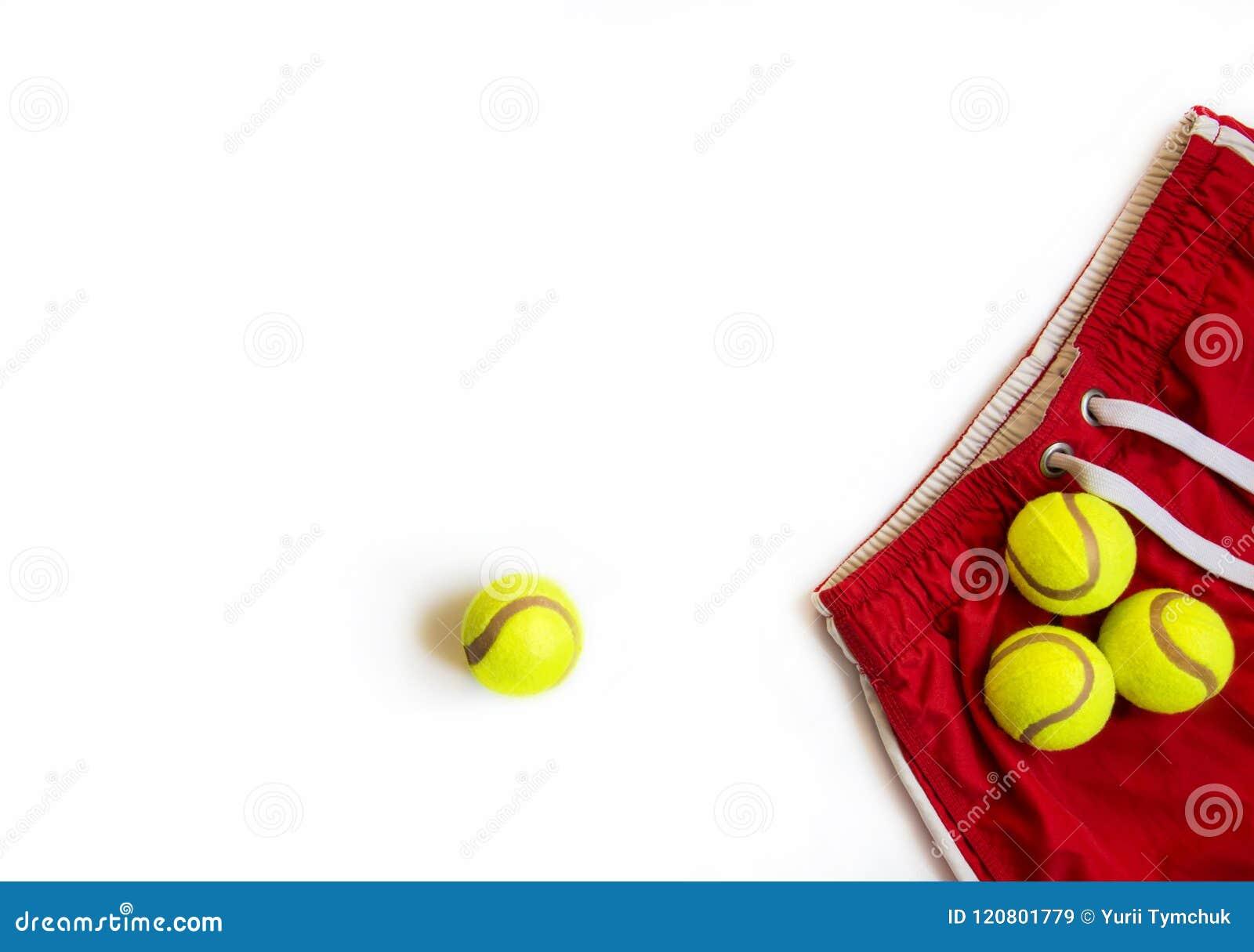 Sport de concept Copiez l espace Trois balles de tennis sur les shorts rouges et une balle de tennis sur le blanc