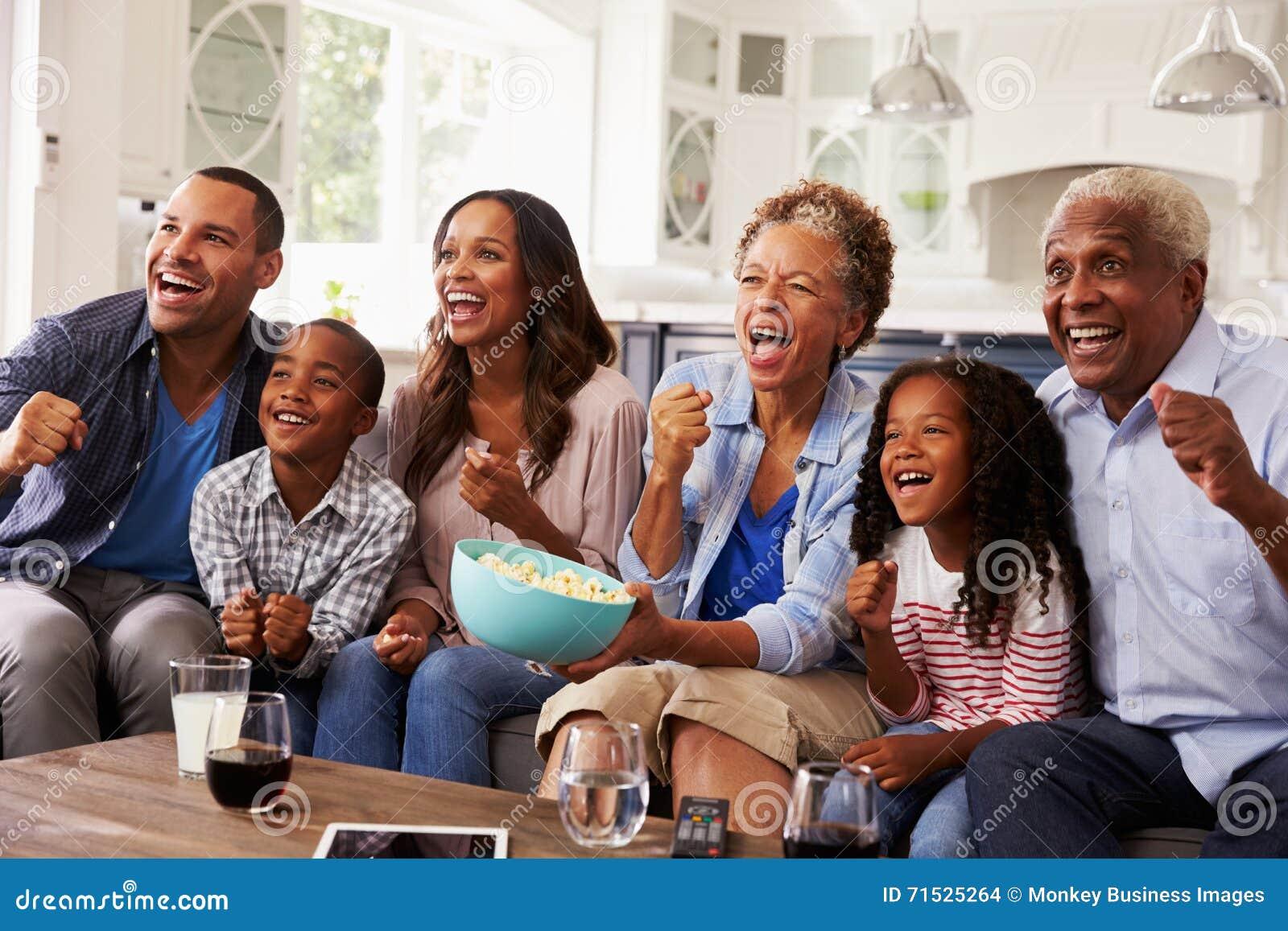Sport de observation de génération de famille multi de noir à la TV à la maison