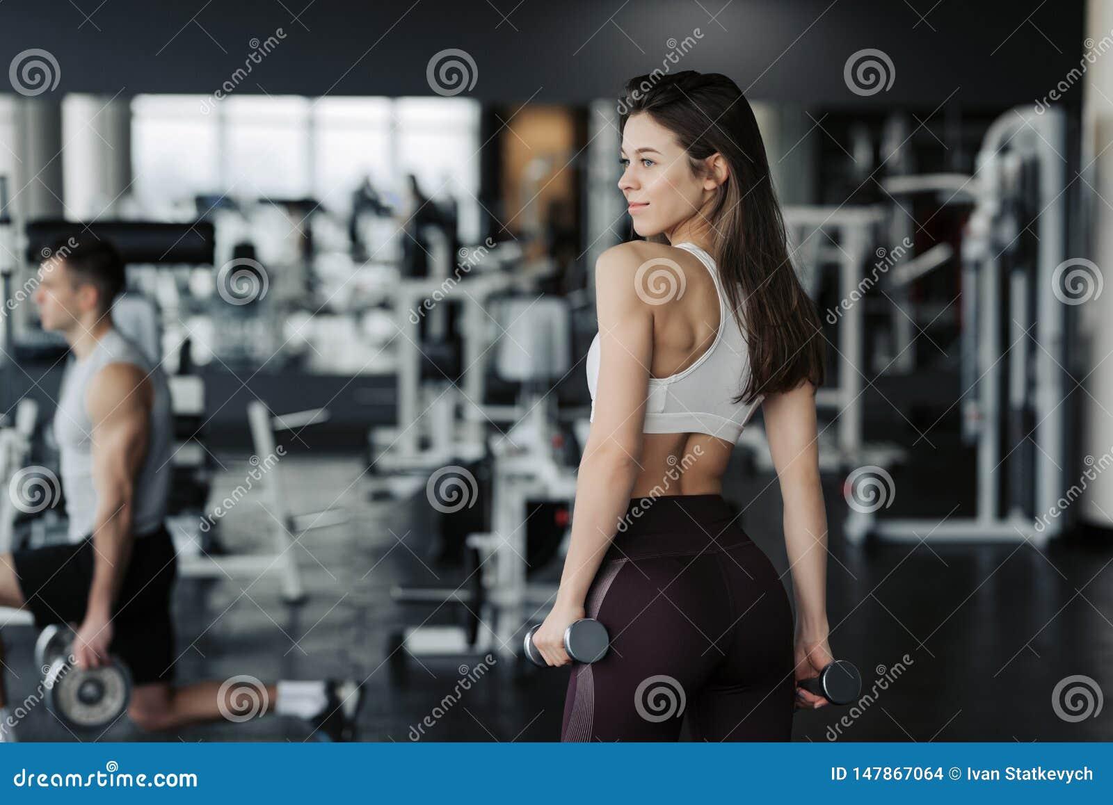 Sport Den idrotts- konditionkvinnan som pumpar upp, tr?nga sig in med hantlar Sexig konditionflicka f?r brunett i sportkl?der med
