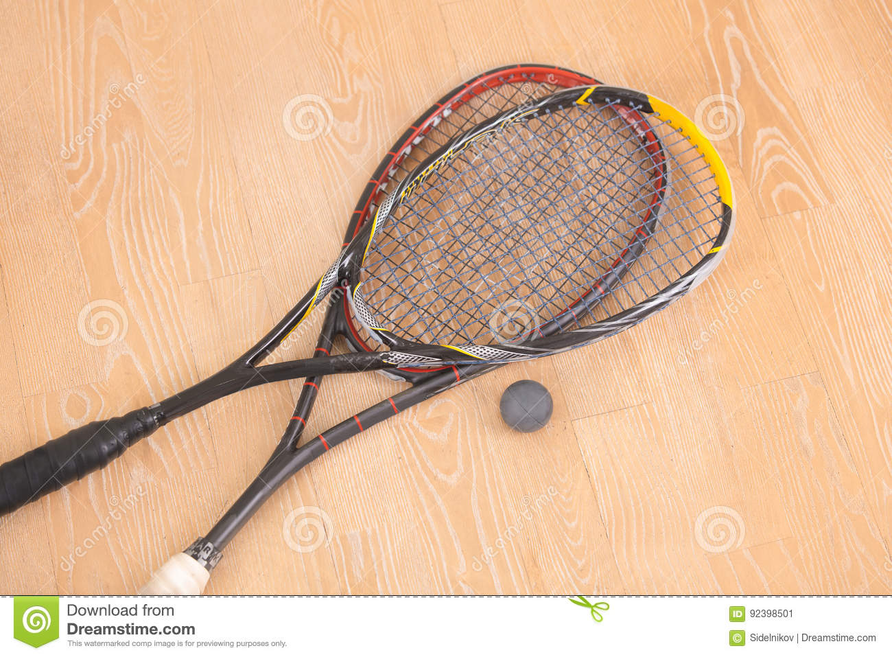 Sport equiment rackets and ball on floor