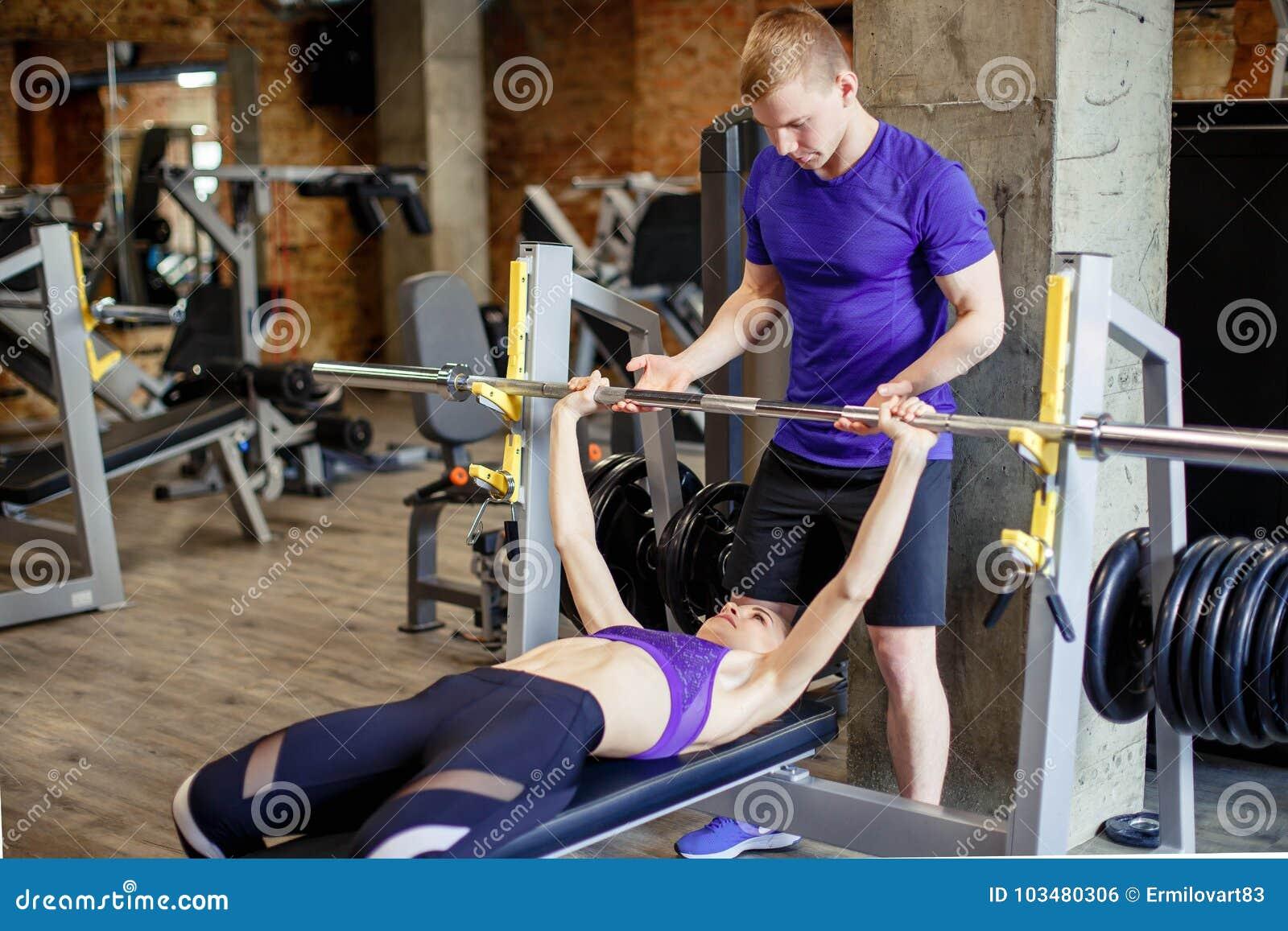 Sport, fitness, het bodybuilding en mensenconcept - de vrouw en de persoonlijke trainer met barbell versperren verbuigingsspieren
