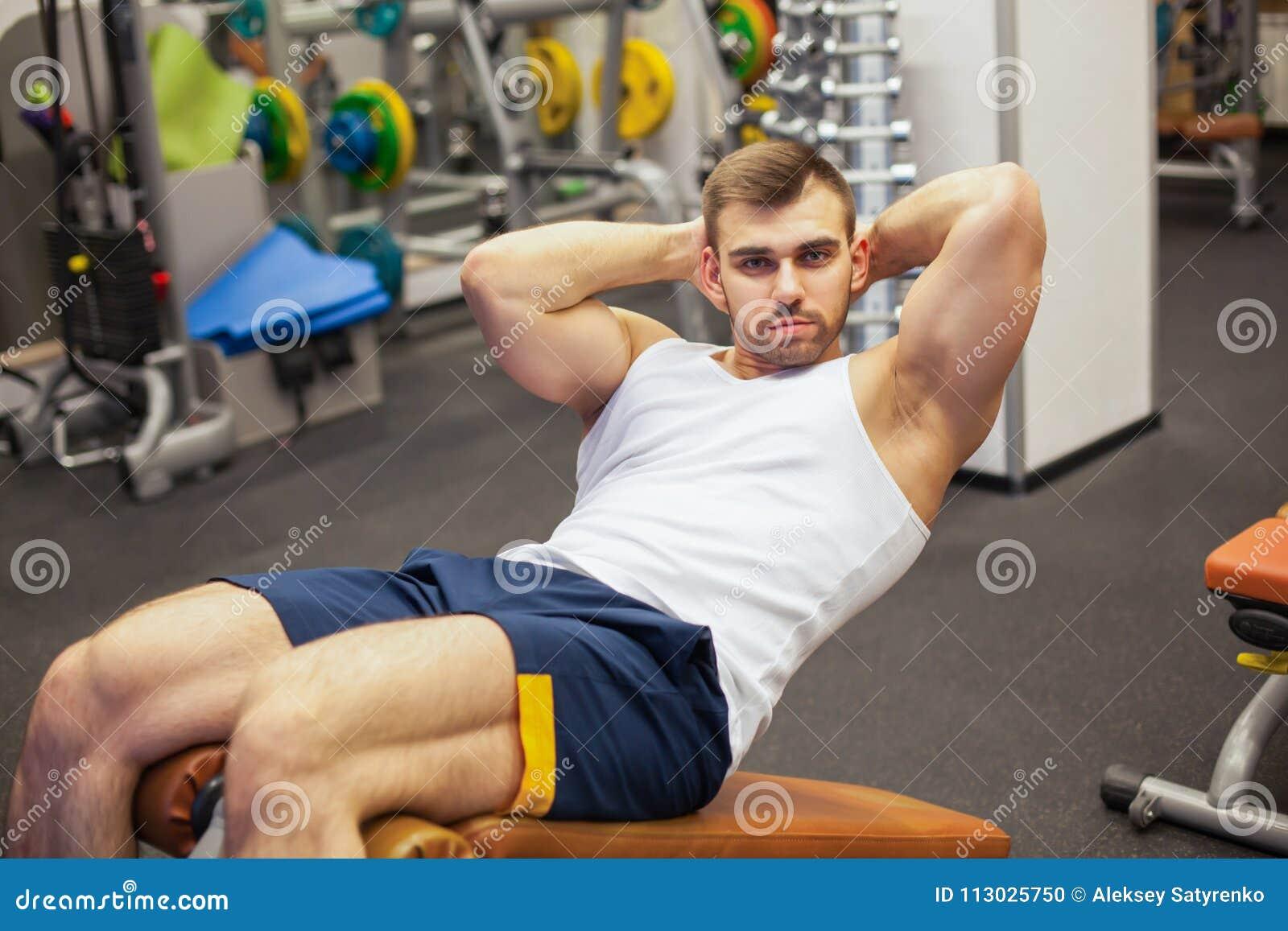 Sport, fitness, het bodybuilding, levensstijl en mensenconcept - jonge mens die zitten-op de buikpers van de oefeningenbank binne