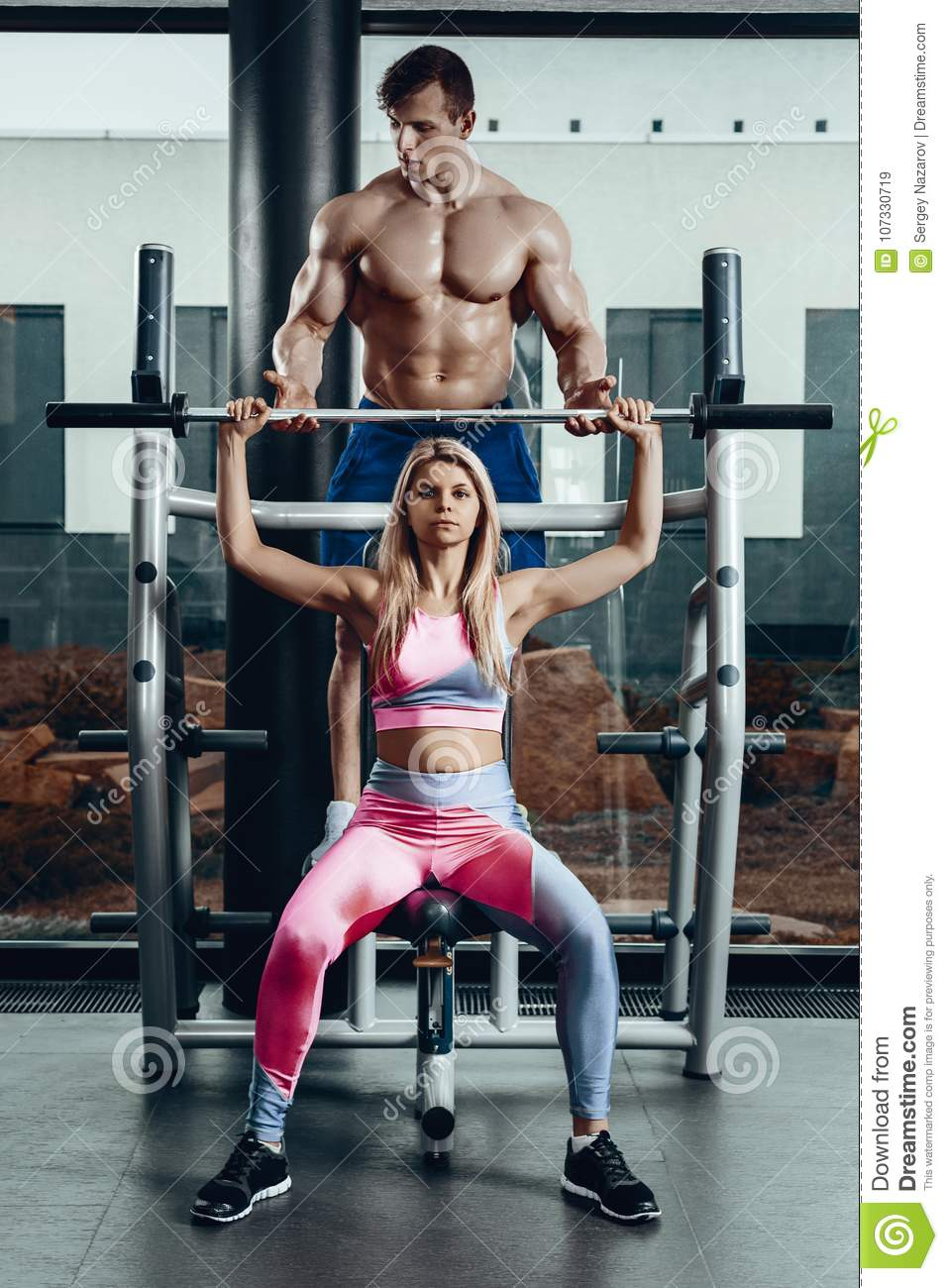 Sport, fitness, teamwork, bodybuilding and people concept - young woman and personal trainer with barbell flexing