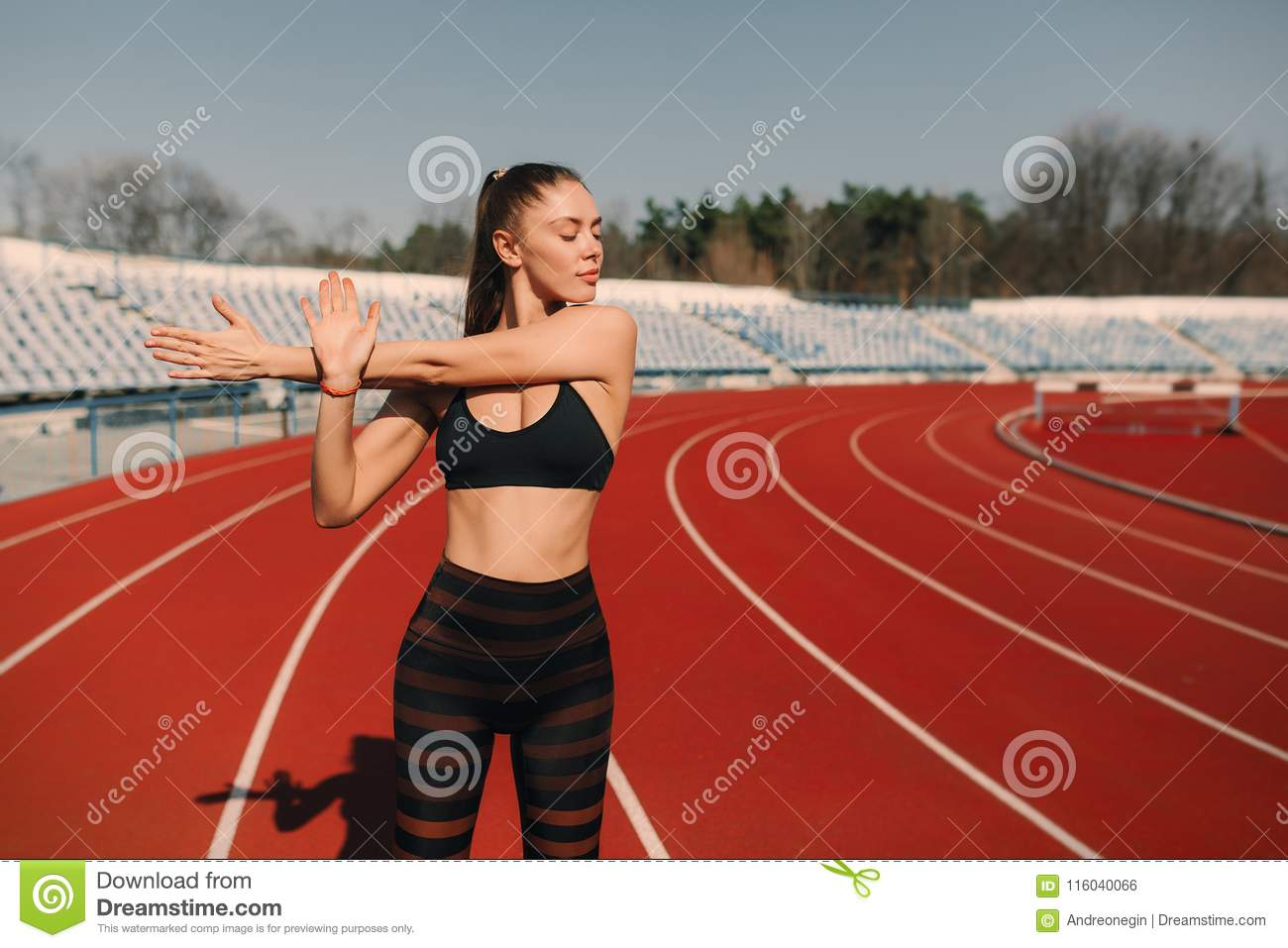 Sport fitness woman stretching on the stadium.Sport blond girl stretching arms in sport running arena with many tracks.