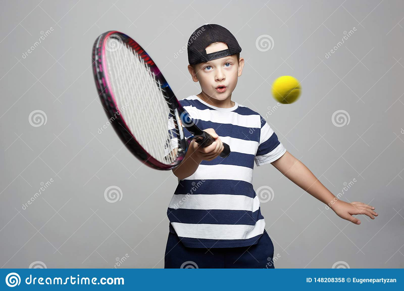 Sport kid. Child with tennis racquet and ball