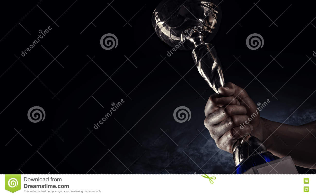 Sport. Man s hand holding up a gold trophy cup