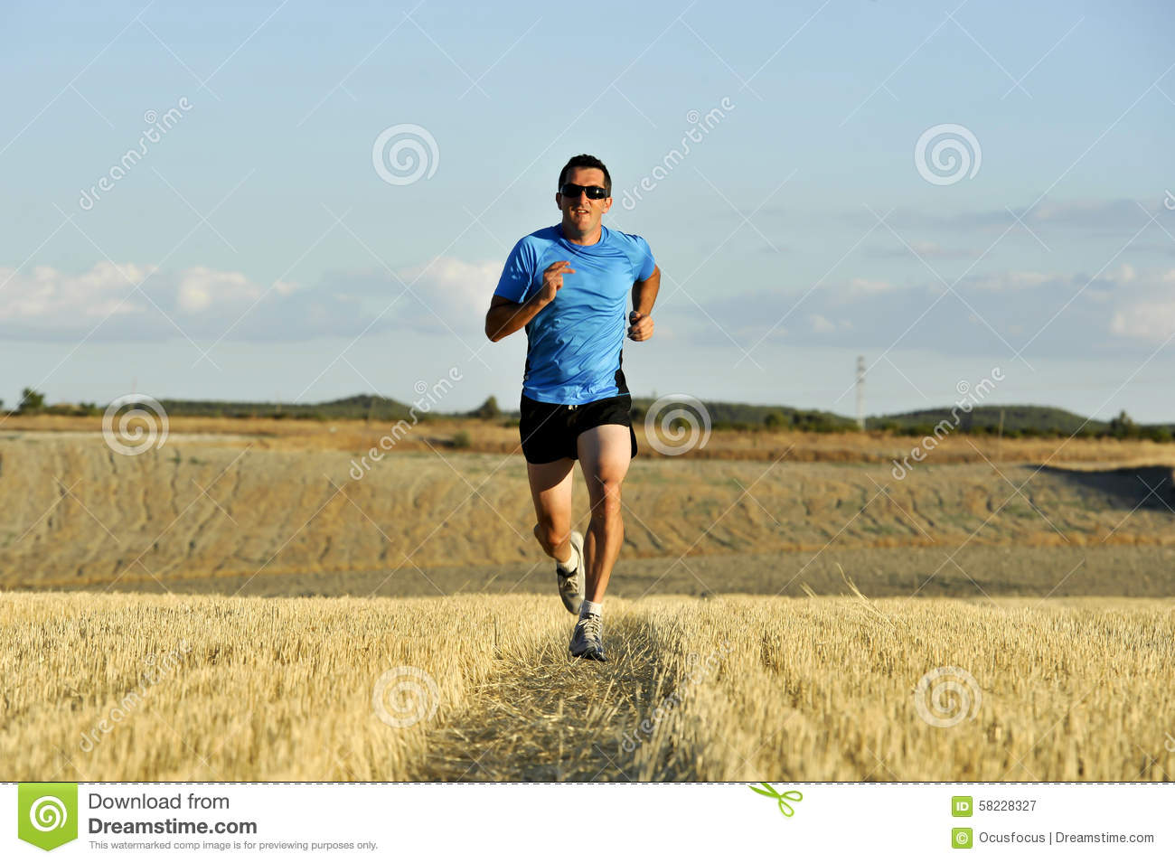 Sport man with sunglasses running outdoors on straw field ground in frontal perspective