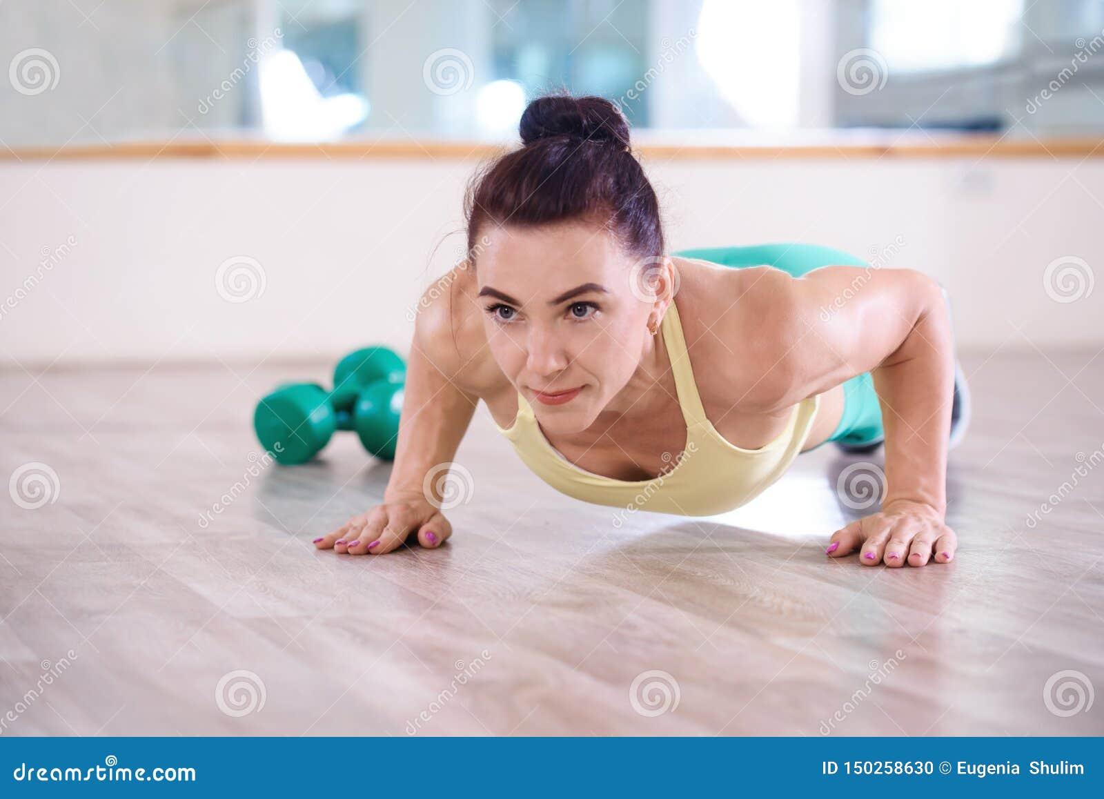 Sport Mooi atletisch meisje die opdrukoefeningenoefeningen in de gymnastiek doen