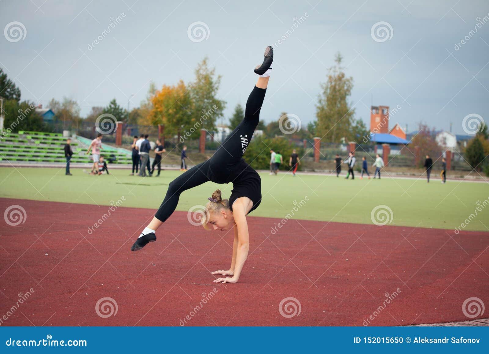 Sport nastoletnia dziewczyna w stadium wykonuje gimnastycznych ćwiczenia