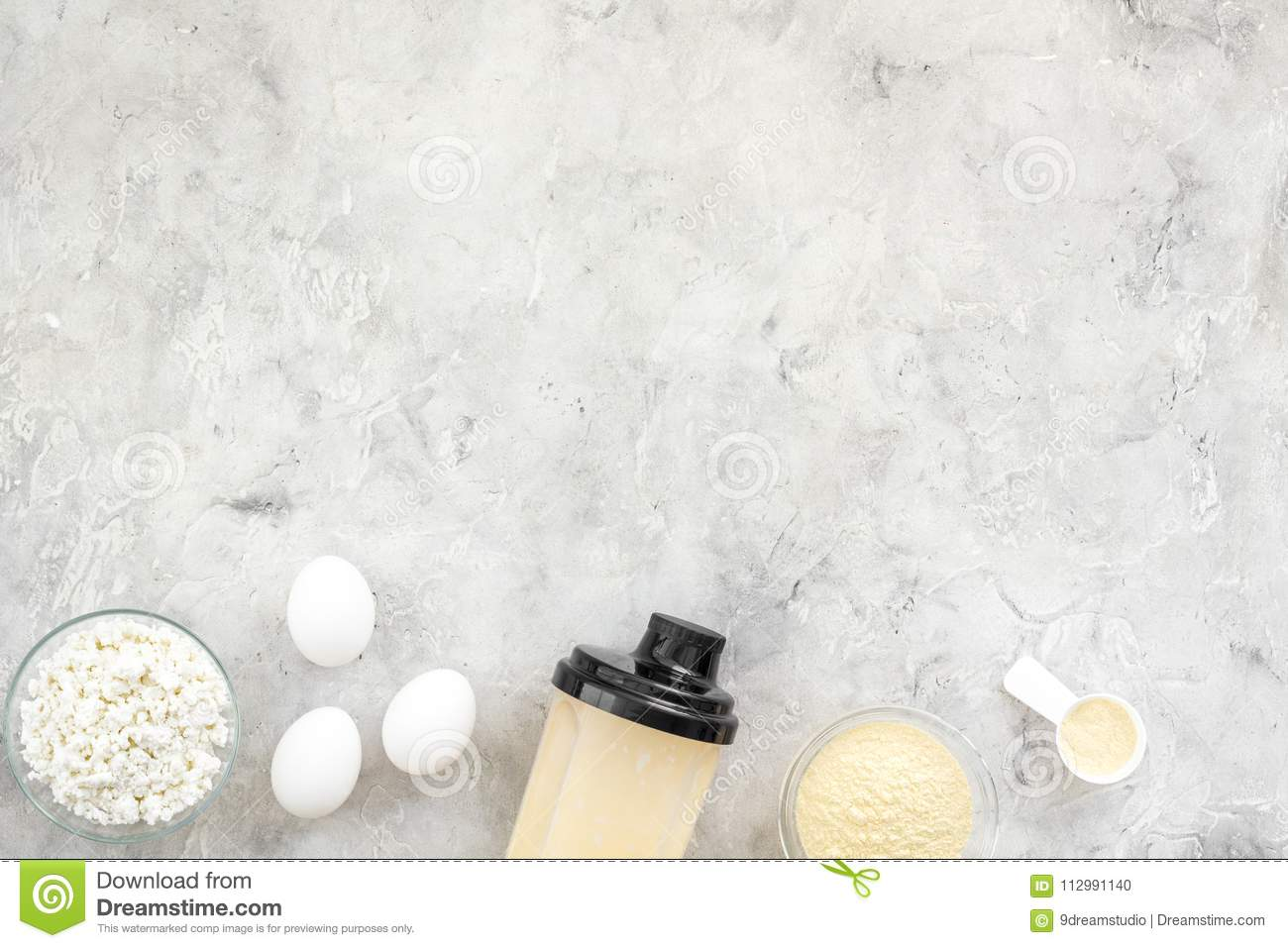 Sport nutrition set with protein powder for cocktail and eggs gray stone background top view space for text