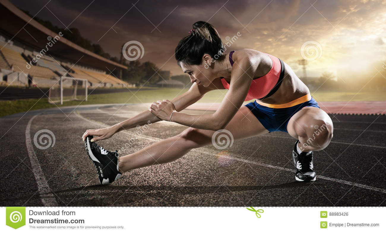 Sport. Runner stretching on the running track.