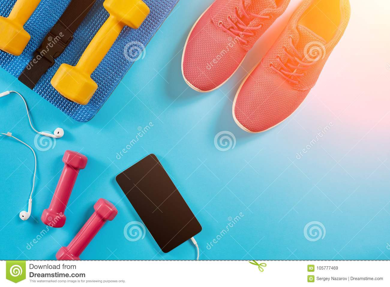 Sport shoes, dumbbells and mobile phone on blue background. Top view. Fitness, sport and healthy lifestyle concept. Sun