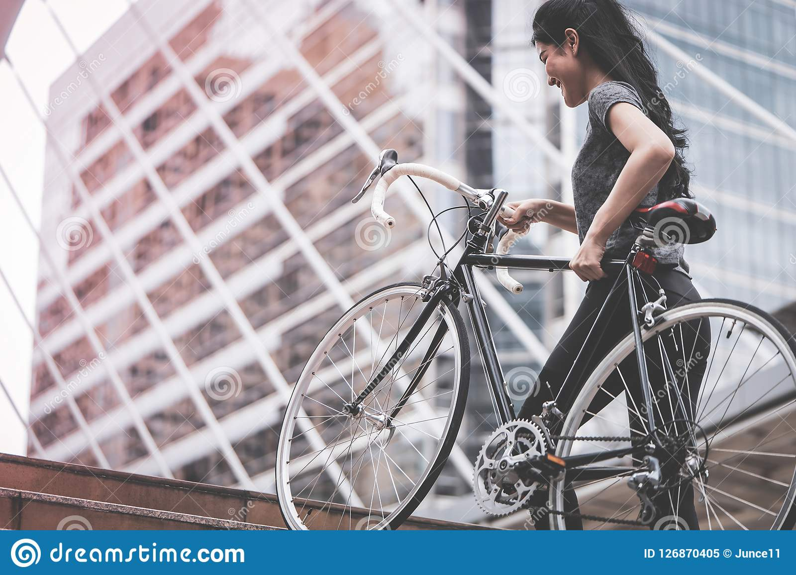 Sport woman carrying her bike up the stair. Sport woman is carrying her bike up the stair Royalty Free Stock Photo