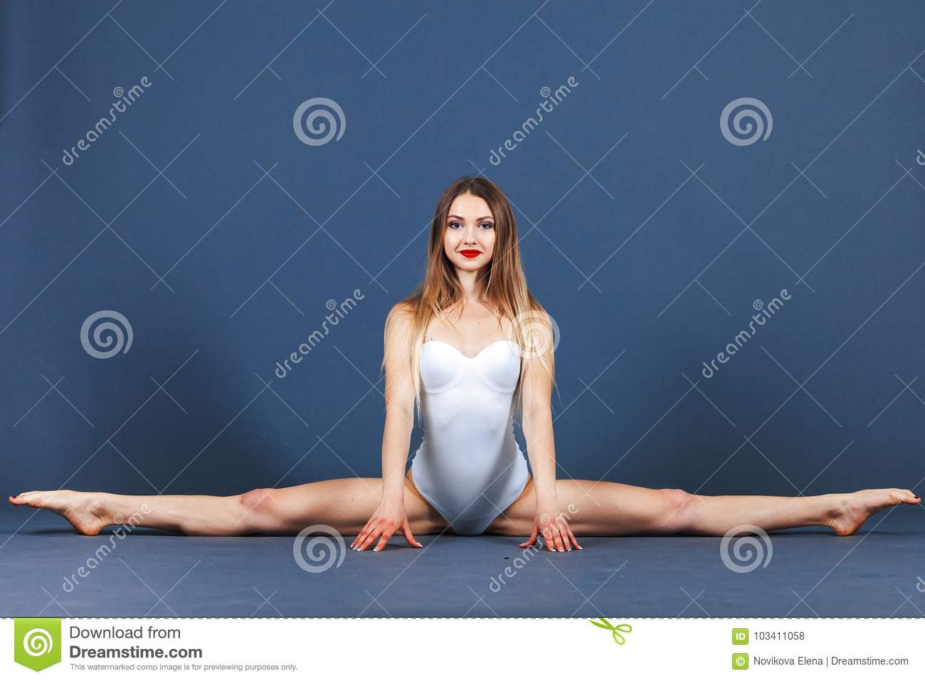 Sport young woman in sportwear bodysuit sits on a twine on a blue background. Studio shot