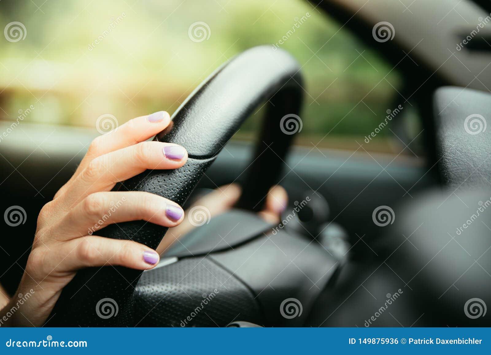 Sporta samochodu kierownica, ręki młoda dziewczyna z purpurowym gwoździa połyskiem