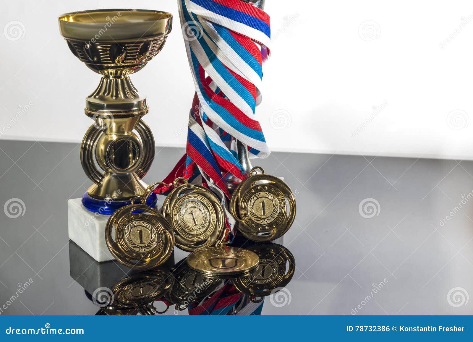 Sportar kuper och medaljen på en svart vit bakgrund