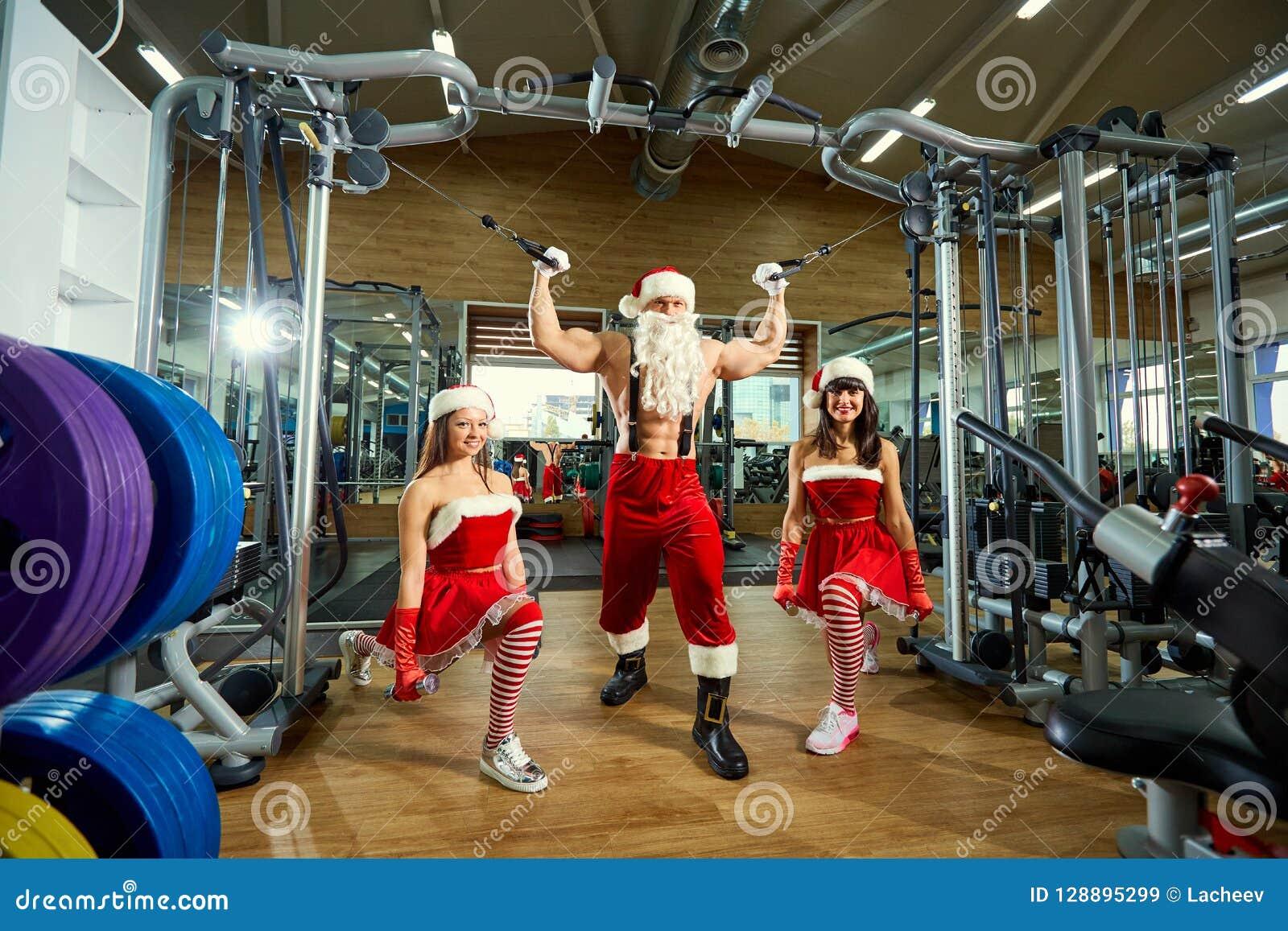 Sportar Santa Claus med flickor i dräkter för jultomten` s i idrottshallen