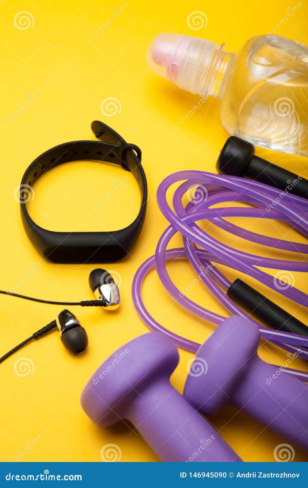 Sportausr?stung Dummköpfe, Springseil, Eignungsarmband, Wasser und Kopfhörer auf einem gelben Hintergrund