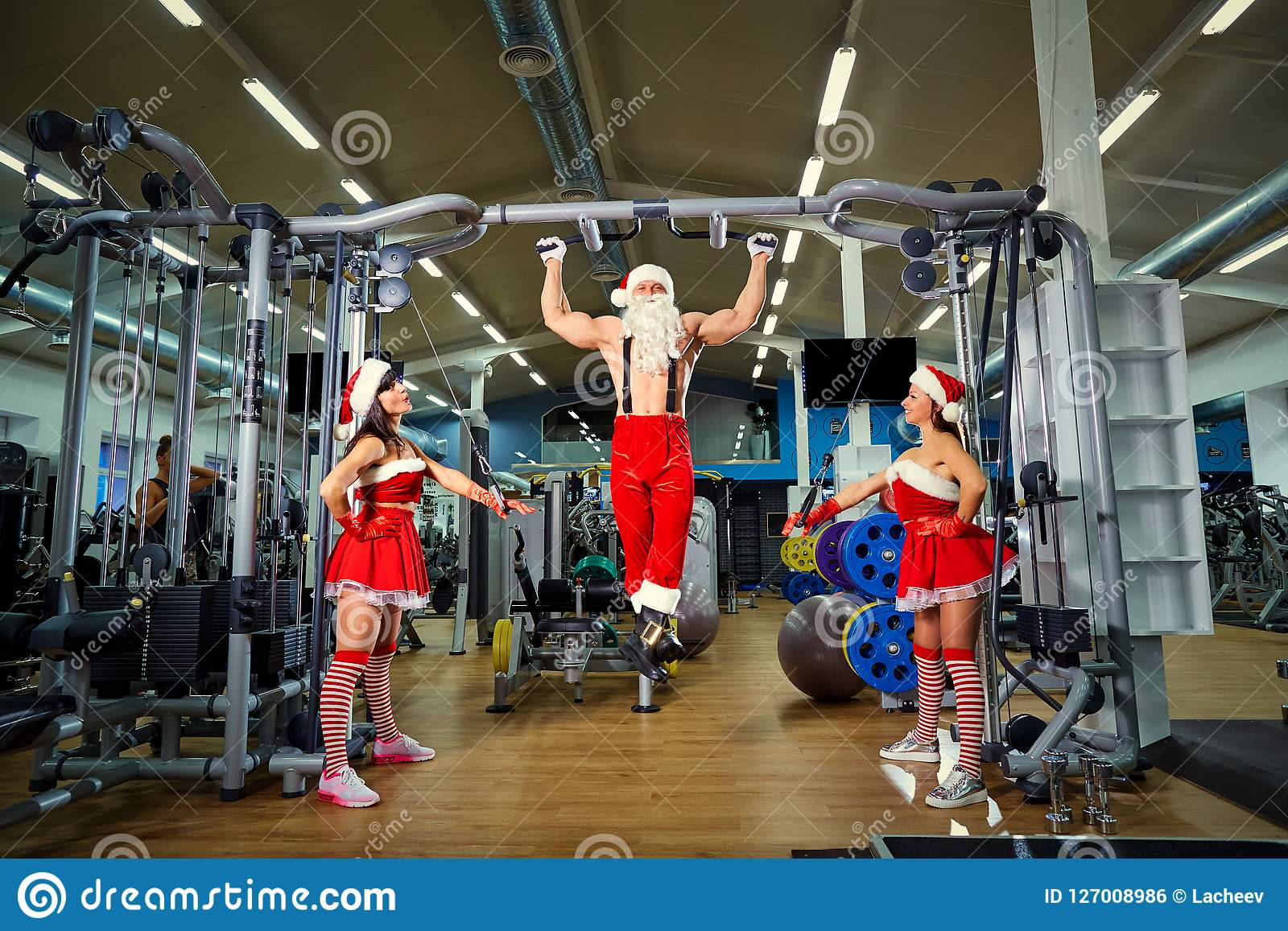 Sporten Santa Claus met meisjes in Kerstman` s kostuums in de gymnastiek