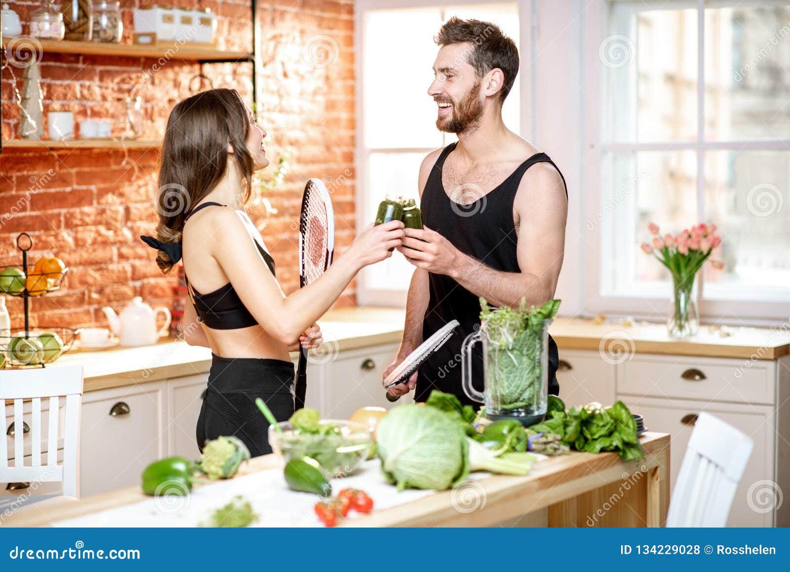 Sportenpaar die gezond voedsel op de keuken thuis eten