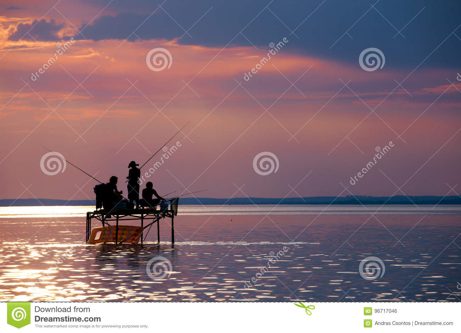 Sportfiskare`-konturer på ett fiske står på solnedgången på sjön Balat