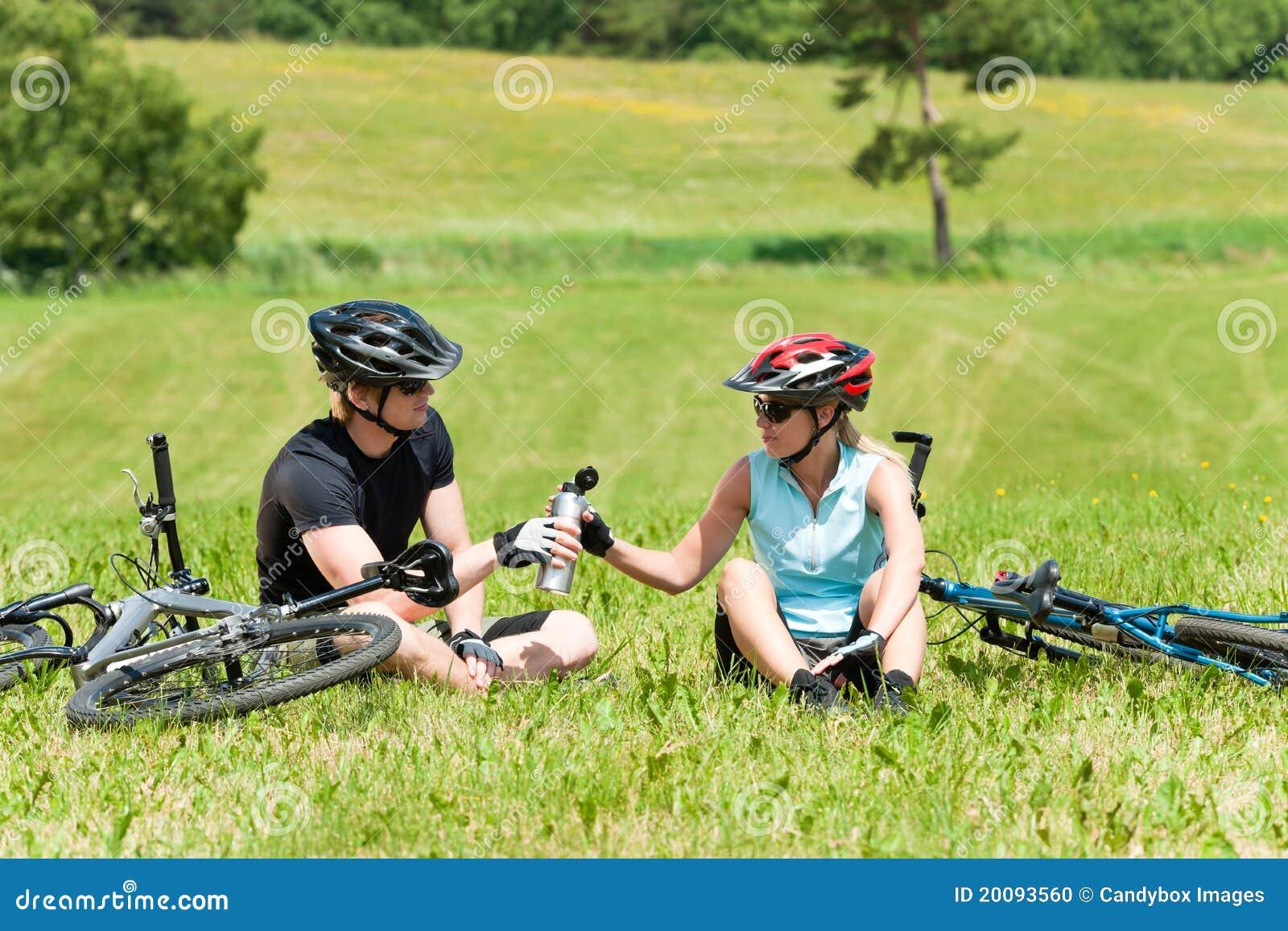 Sportgebirgsradfahrende Paare entspannen sich sonnige Wiesen