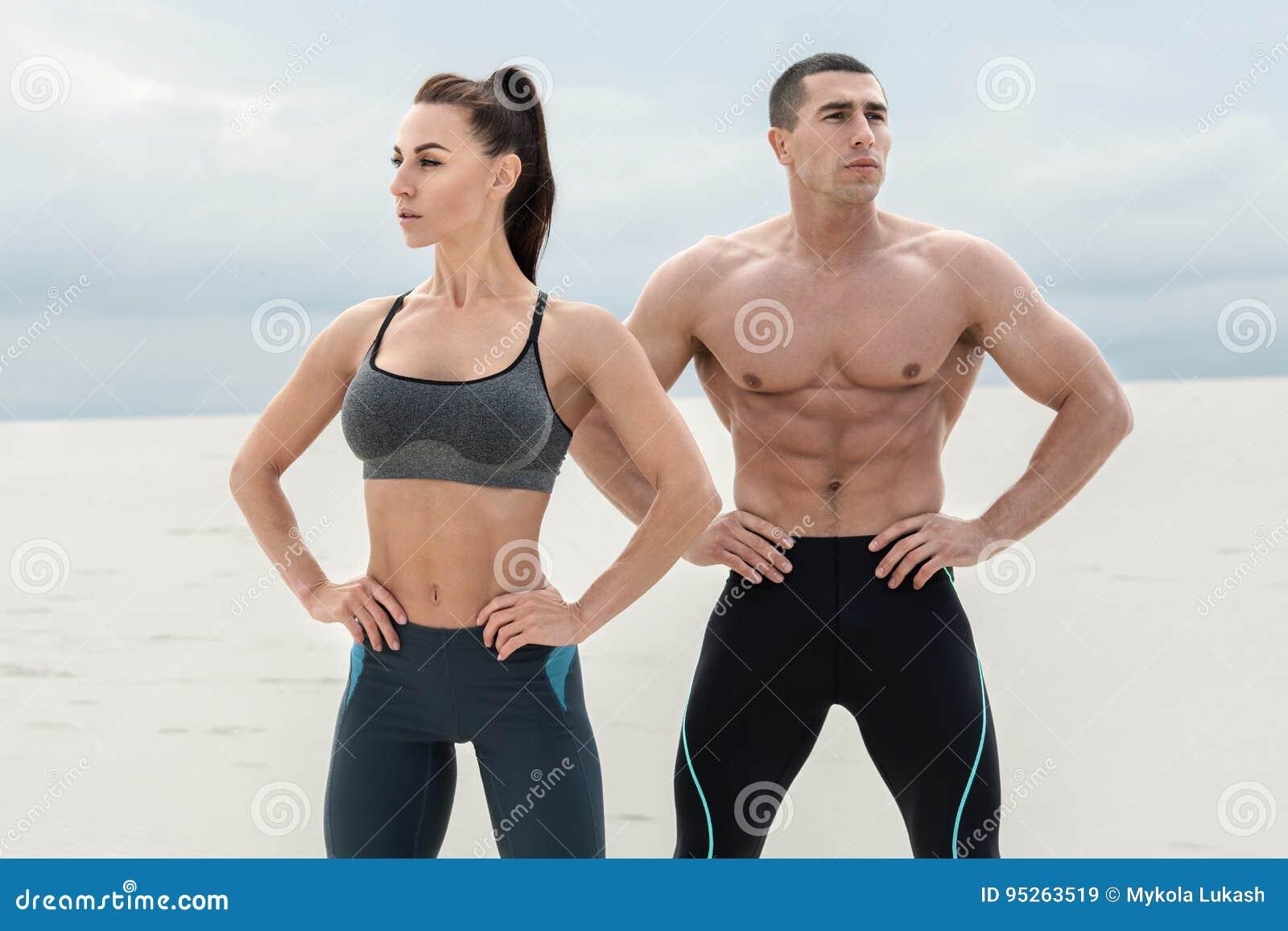 Sportief geschiktheidspaar die spier in openlucht tonen Mooie atletische man en vrouw, spiertorsoabs