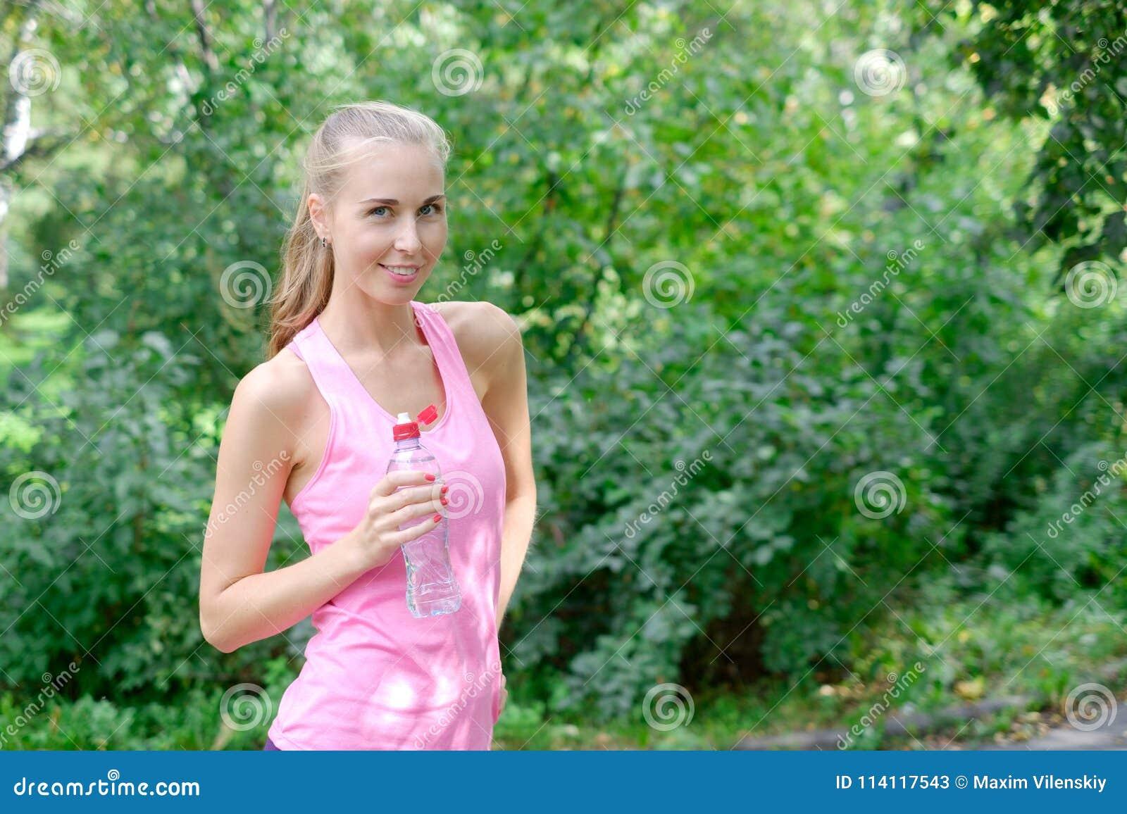 Sportief jong vrouwen drinkwater van de fles Doend Sport Openlucht
