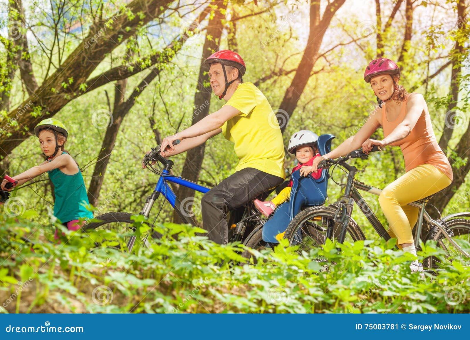 Sportieve familie lopende fietsen in het zonnige bos