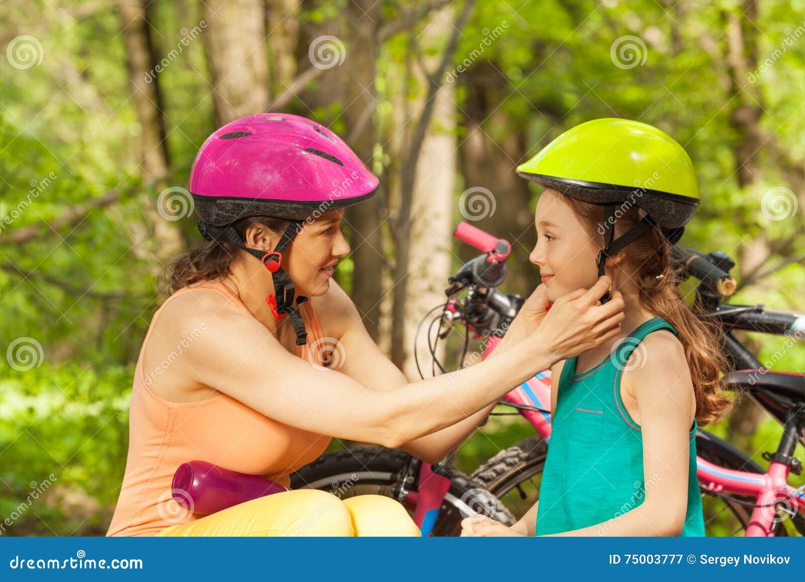 Sportieve moeder die haar dochter helpen aan greephelm