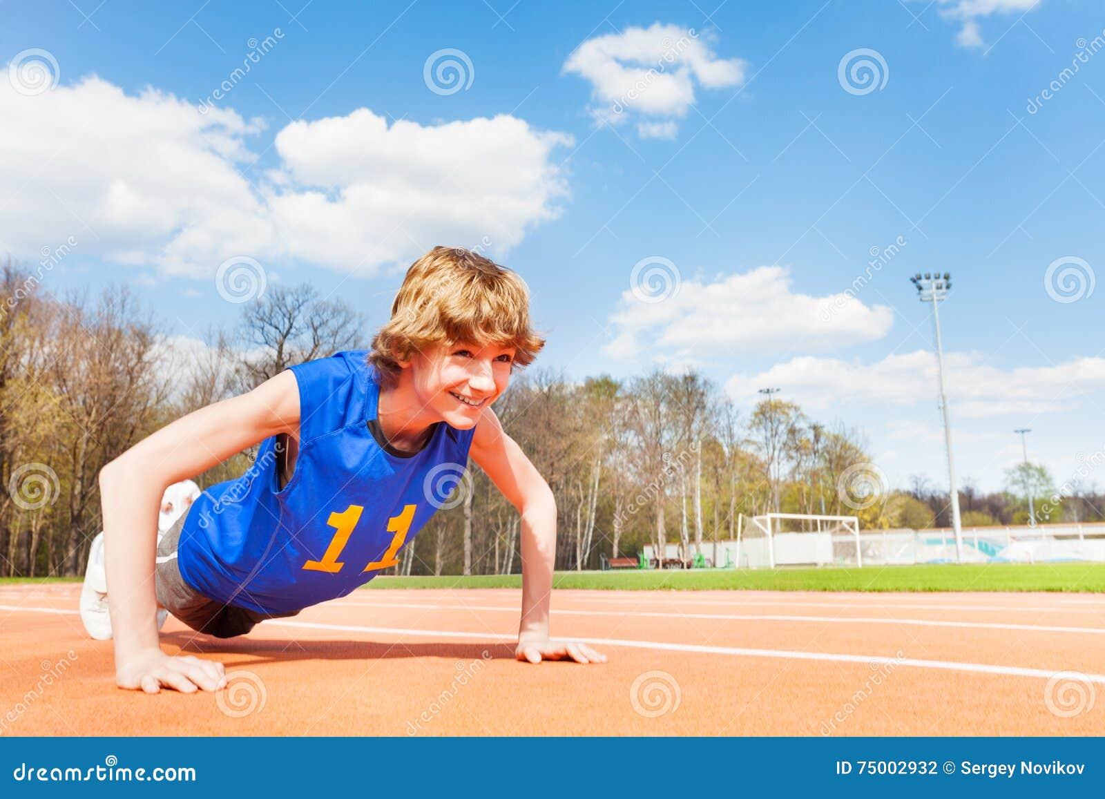 Sportieve tiener die opdrukoefeningenoefeningen doen
