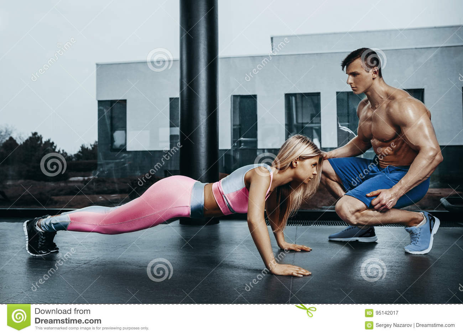Sportieve vrouw die plankoefening opleiding terug en persspieren met trainer doen Sportfitness de macht van de trainingsterkte